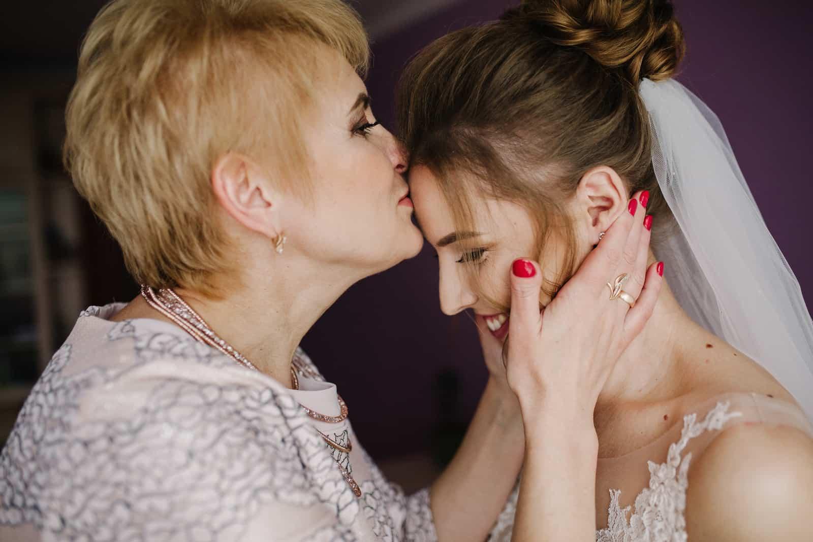 Die Mutter der Braut küsst sie auf die Stirn