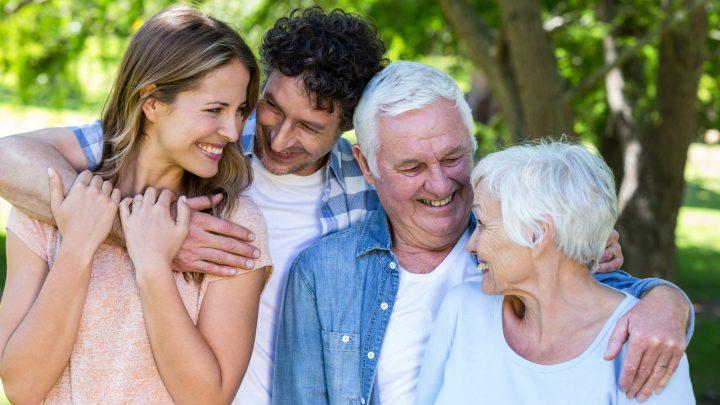 Lächelnde Familie, die in einem Park umarmt