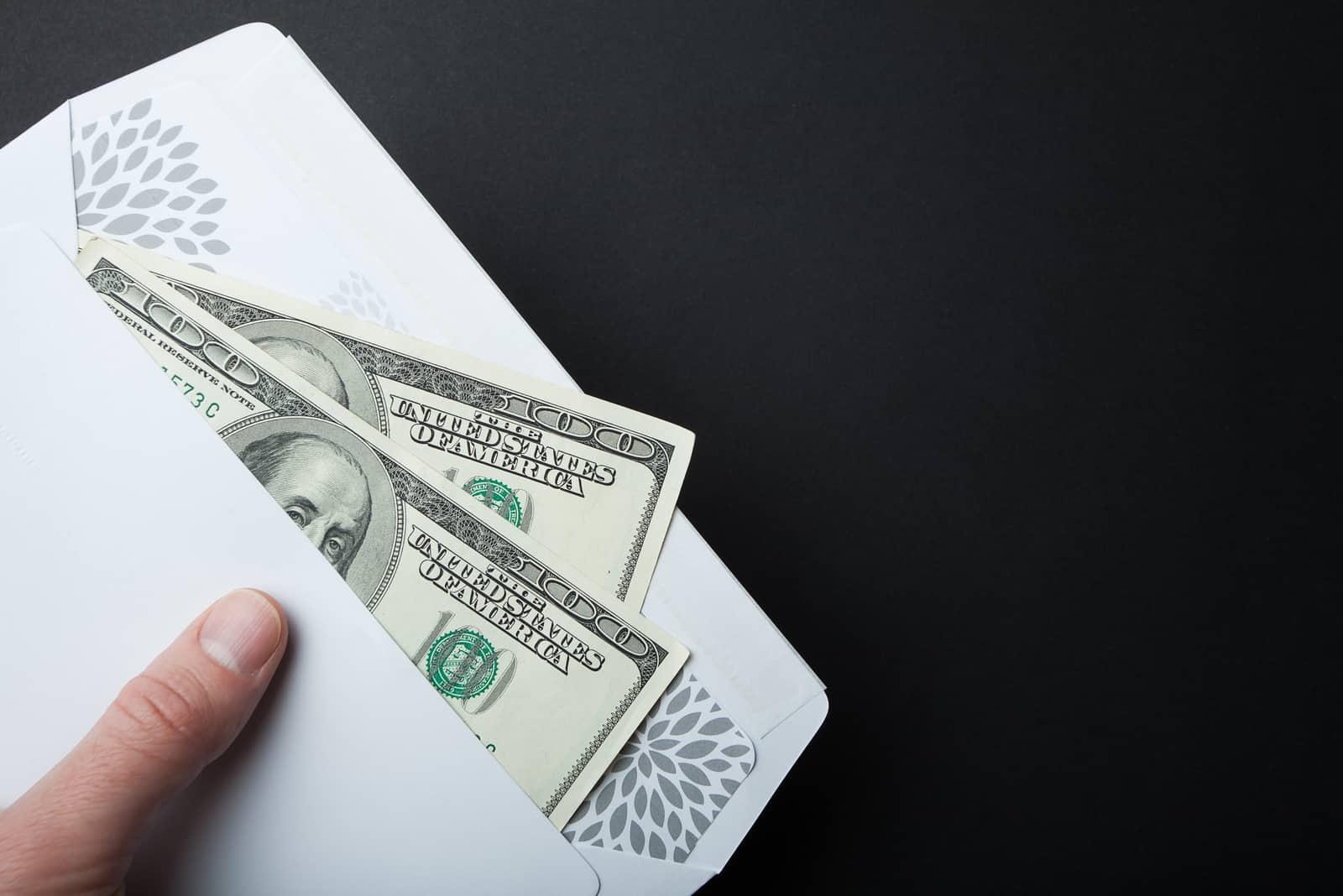Dollar Bestechung in einem Umschlag auf einem schwarzen Hintergrund, leerer Raum für Text.