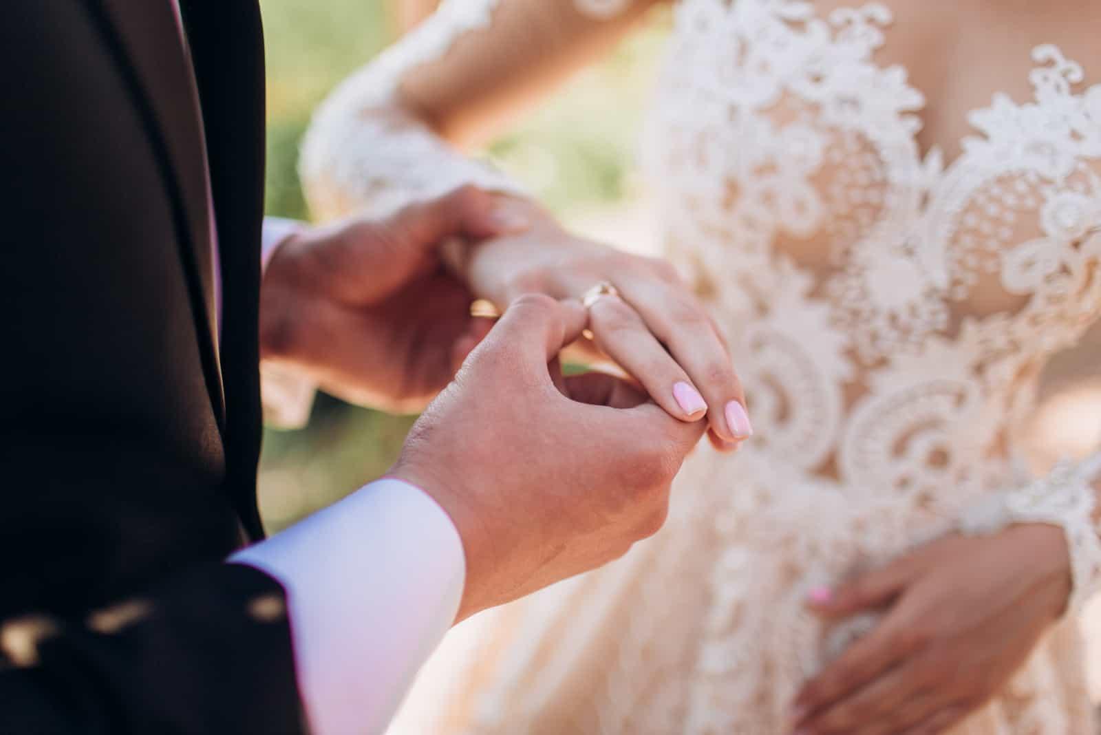 Eheringe in den Händen von Braut und Bräutigam.