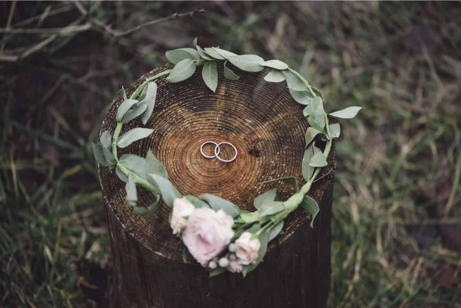 Eheringe in einem Blumenstirnband auf einem Holzstumpf