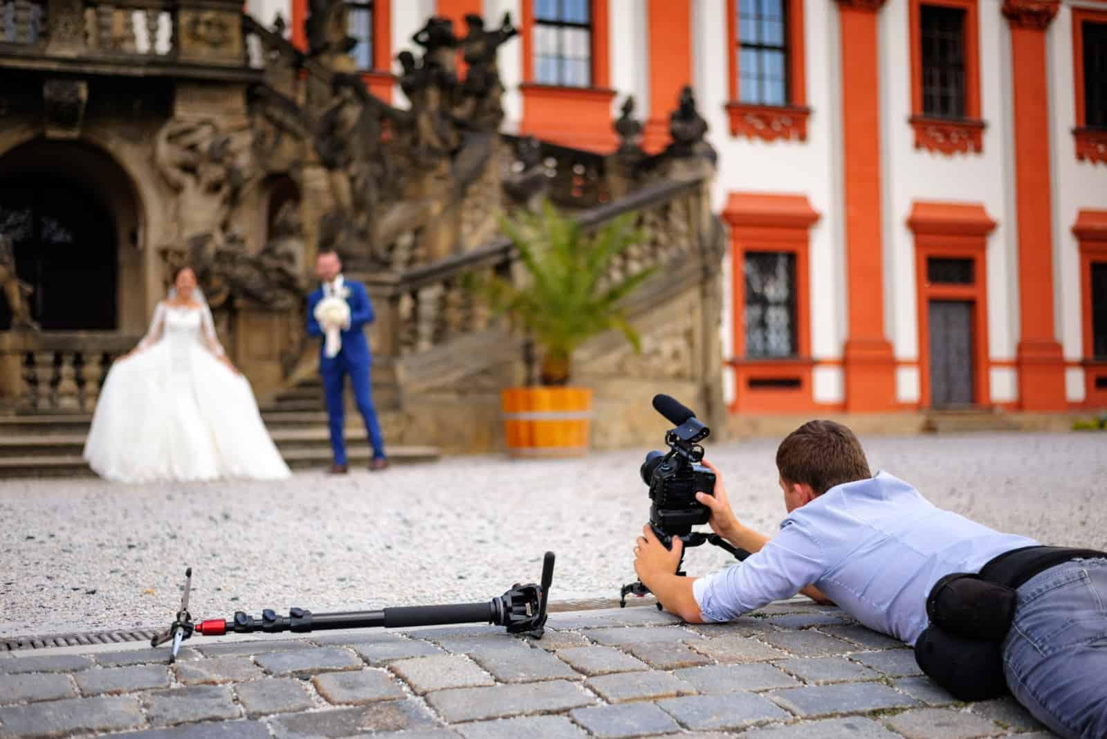 Ein Kameramann liegt auf dem Boden, um das Brautpaar zu filmen