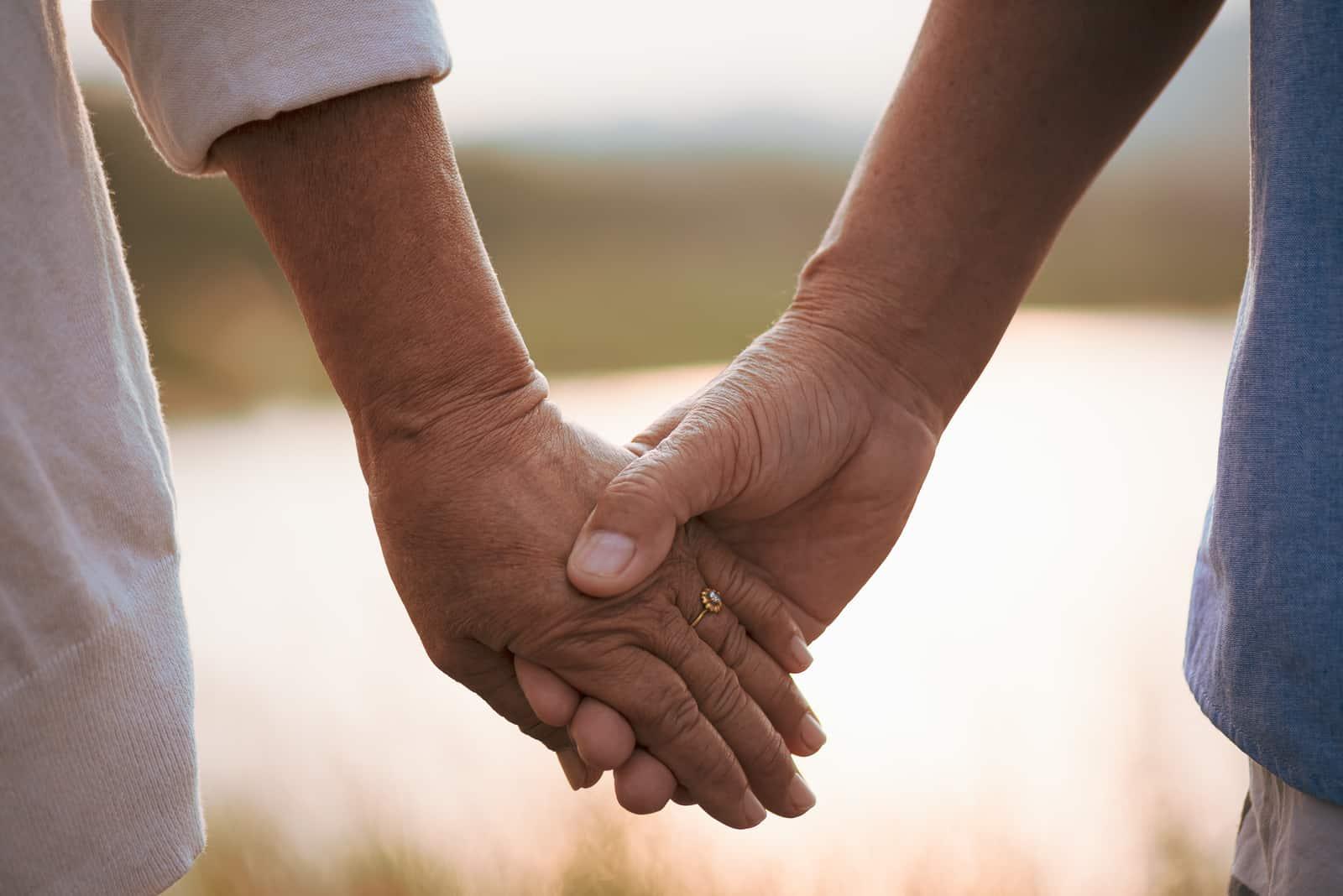 Ein glückliches älteres Paar, das Hand während Sonnenuntergang hält