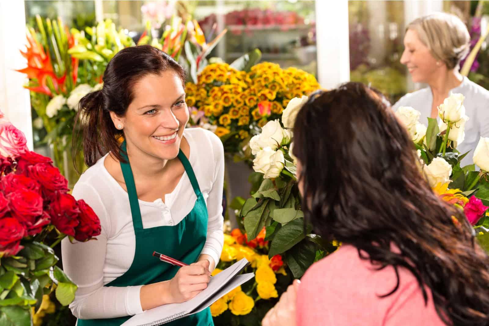 Ein lächelnder Florist spricht mit dem Kunden