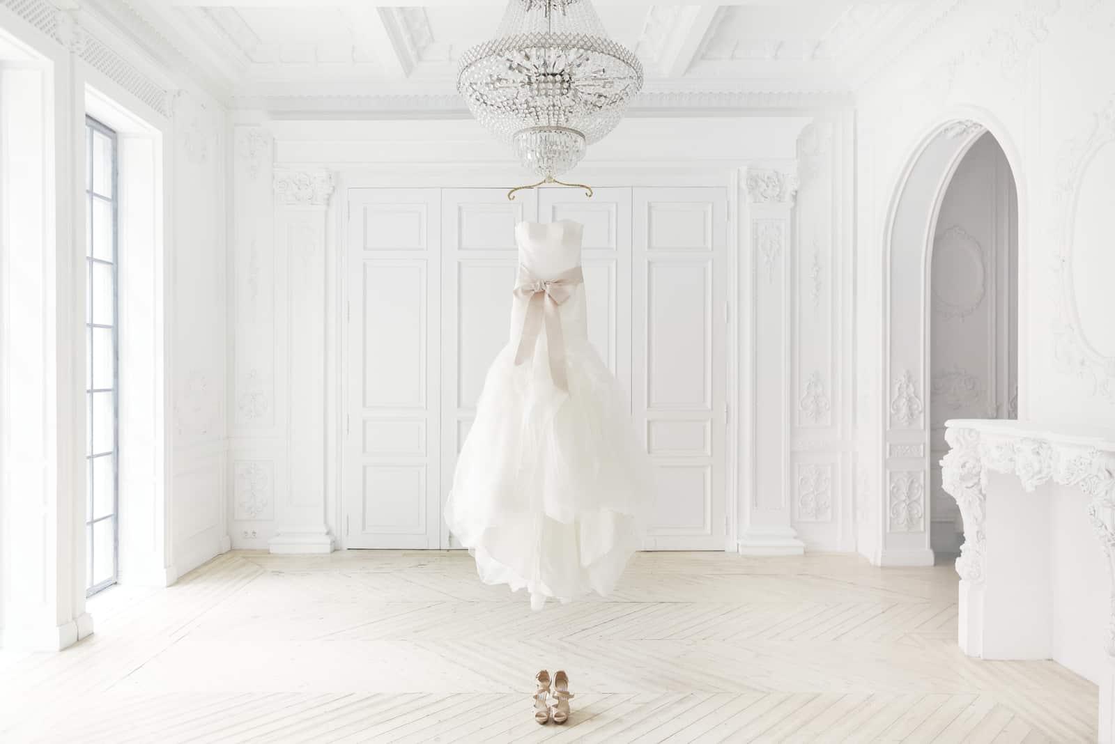 Ein wunderschönes Hochzeitskleid an einer Schnur hing an einem Kronleuchter