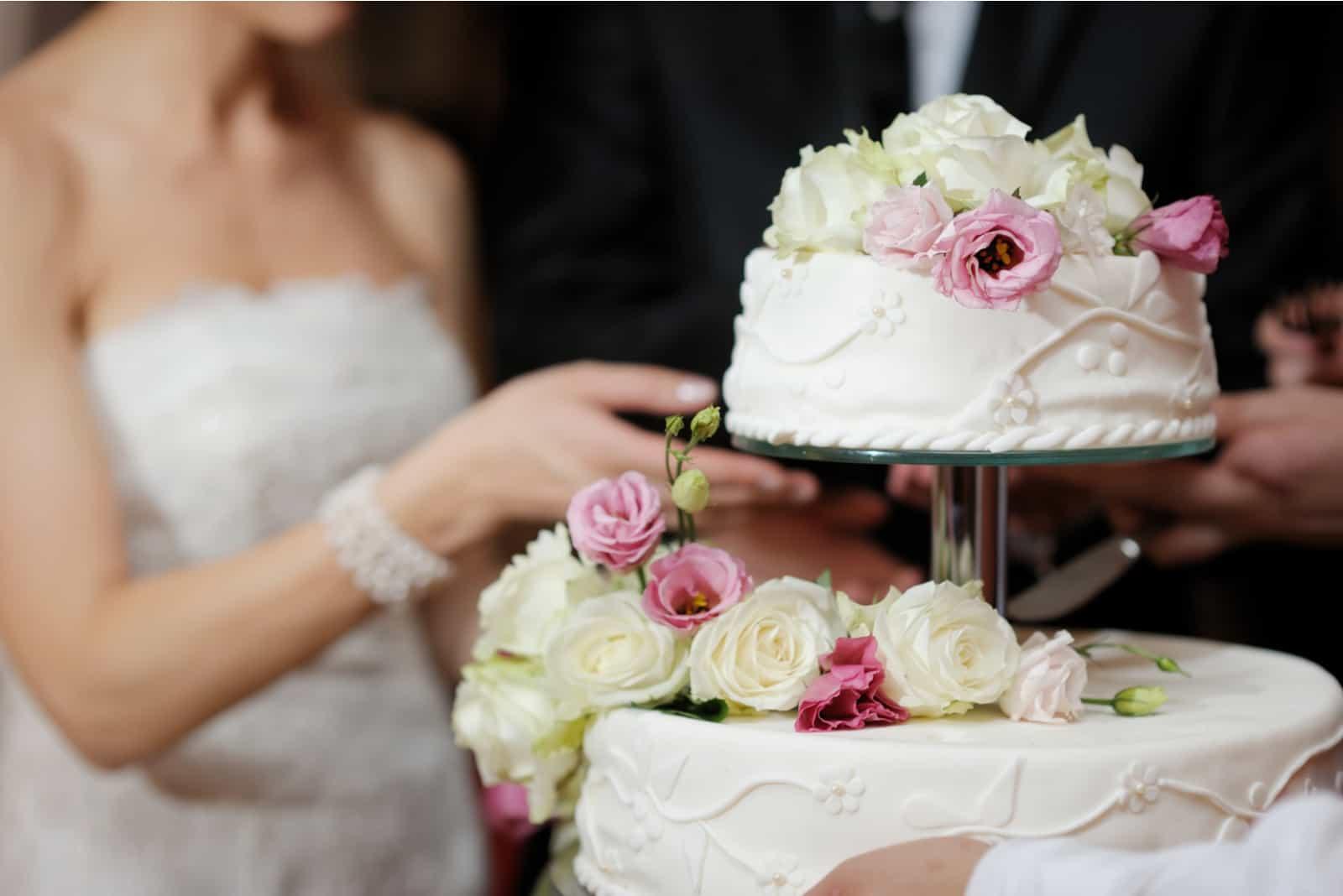 Eine Braut und ein Bräutigam schneiden ihre Hochzeitstorte