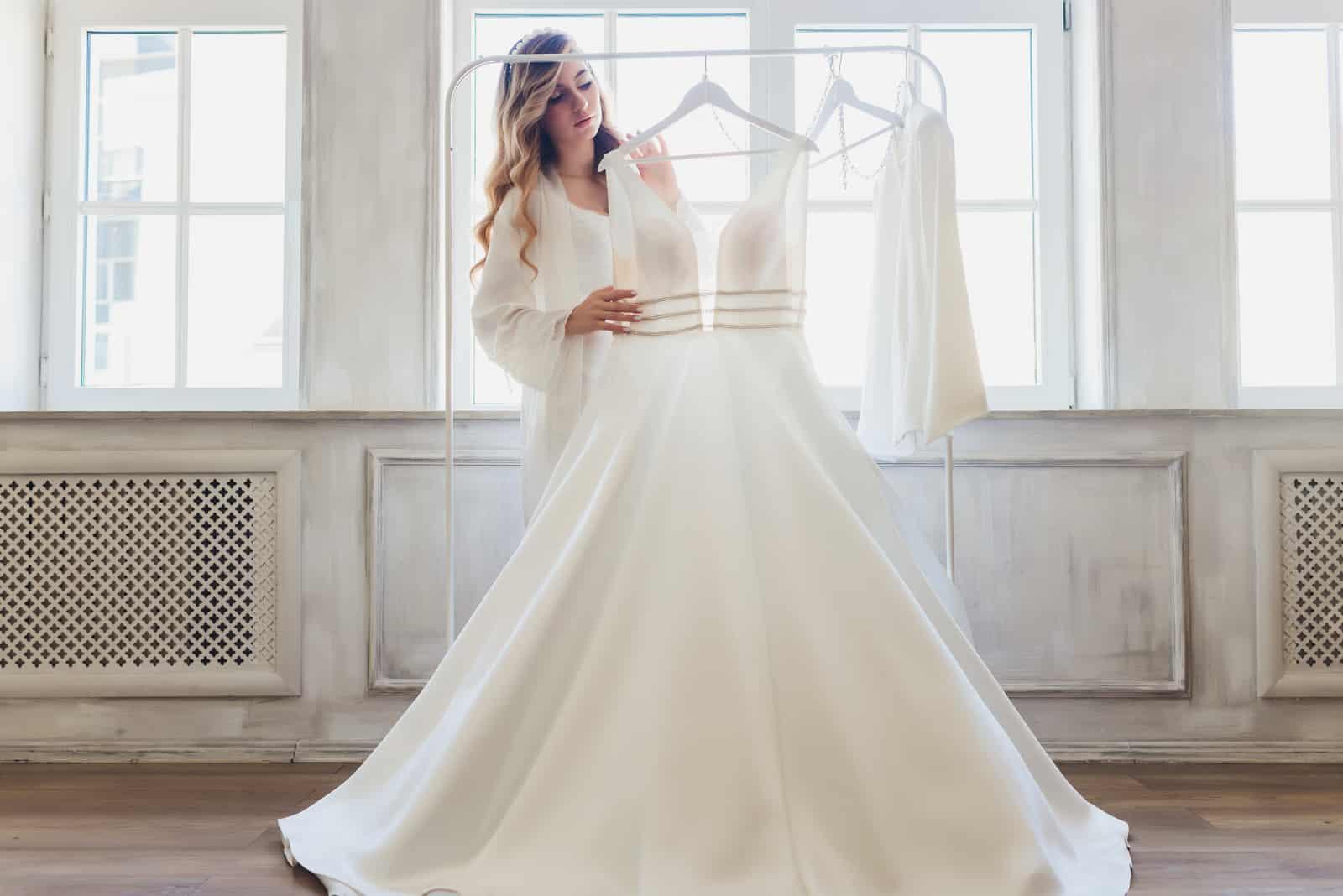 Eine Frau beobachtet ein Hochzeitskleid auf einer Peitsche