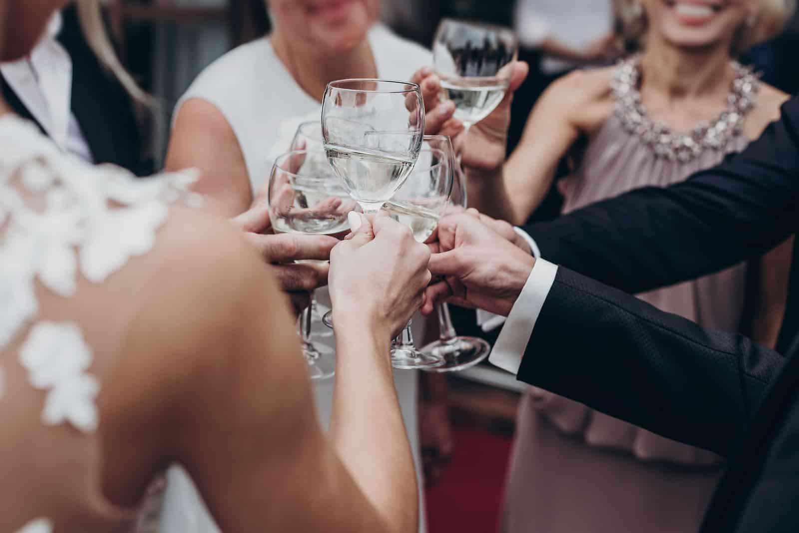 Eine Gruppe von Gästen röstet mit der Braut Champagner