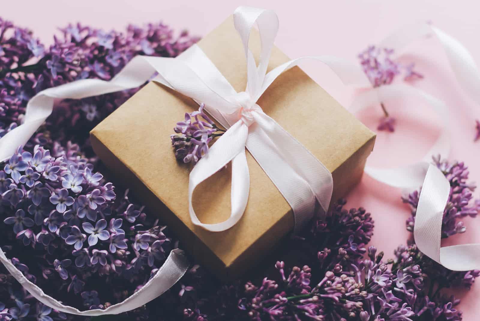 Fliederblumen und Geschenkbox auf rosa Hintergrund