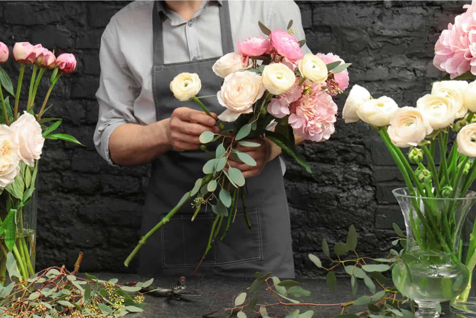 Florist, der schönen Blumenstrauß im Blumenladen schafft