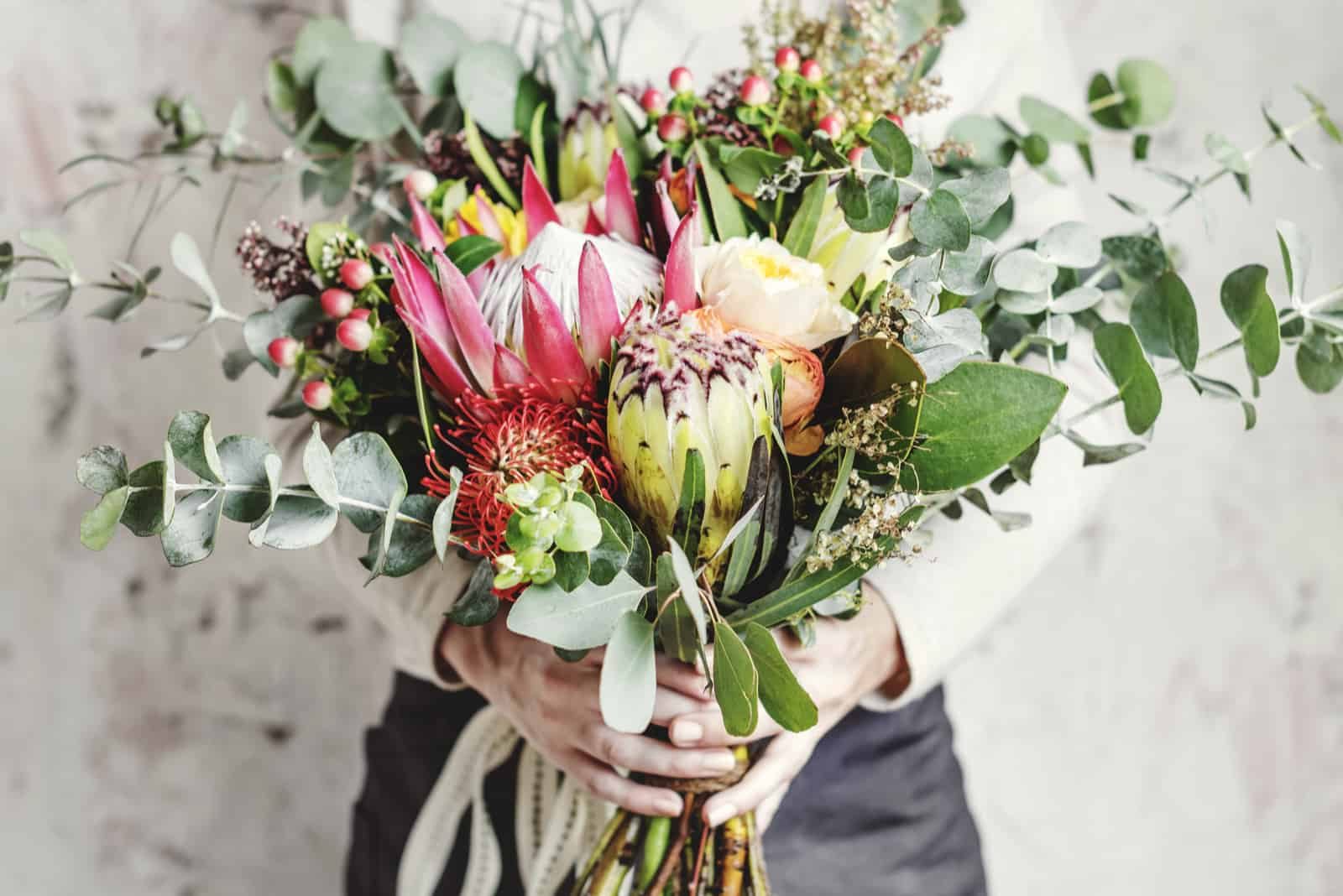 Frauenhände, die schönen Blumenstrauß halten