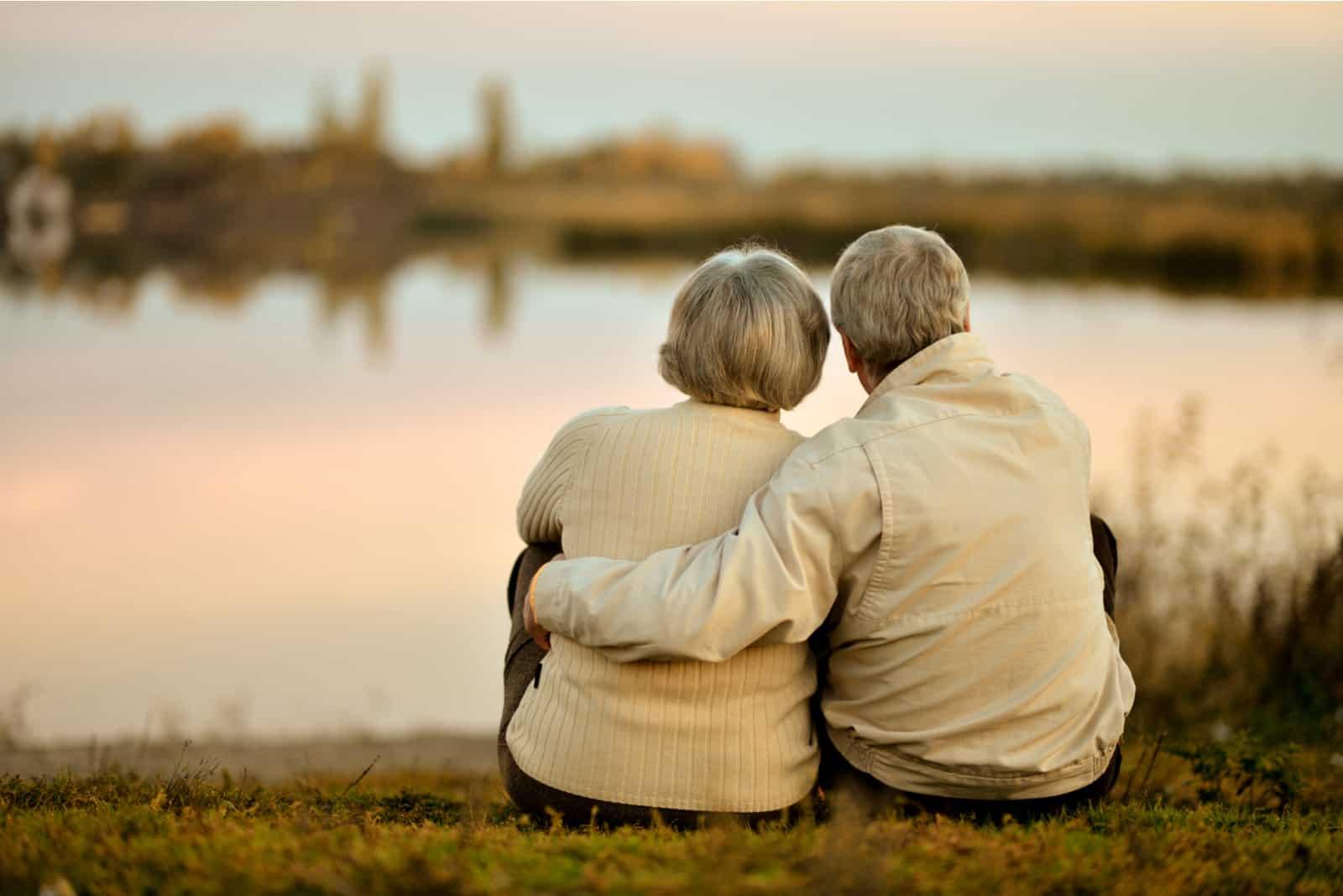 Glückliches älteres Paar, das im Sommer nahe See während Sonnenuntergang sitzt