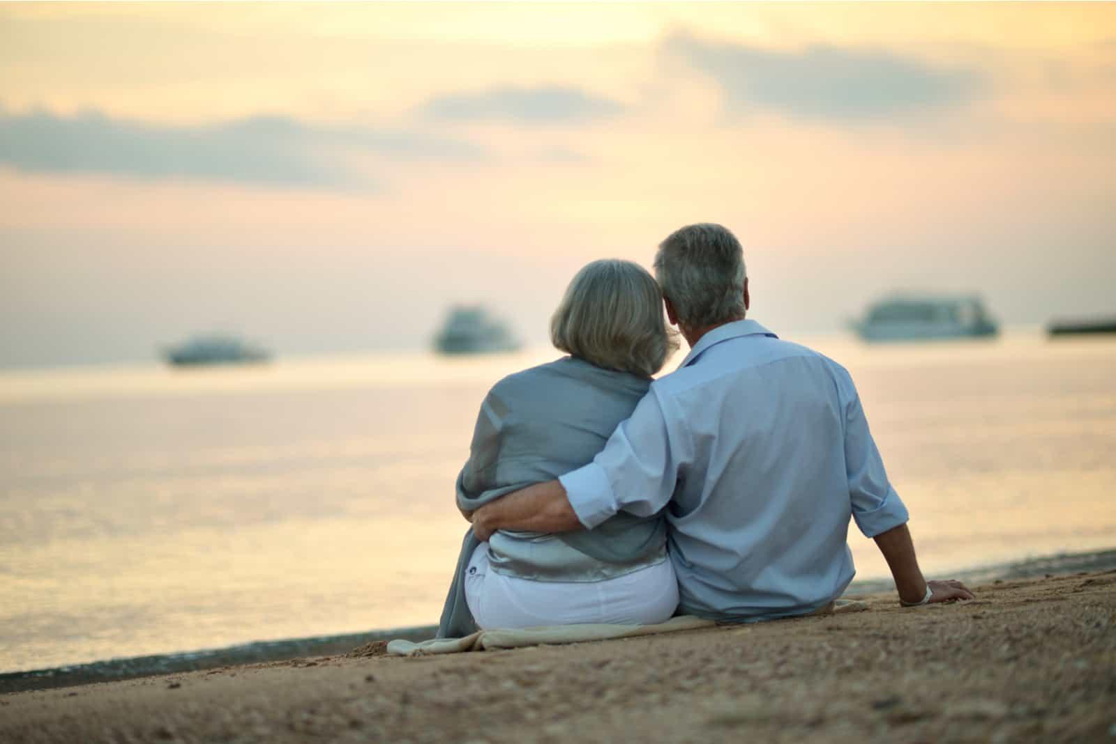 Glückliches reifes Paar, das am Strand bei Sonnenuntergang entspannt