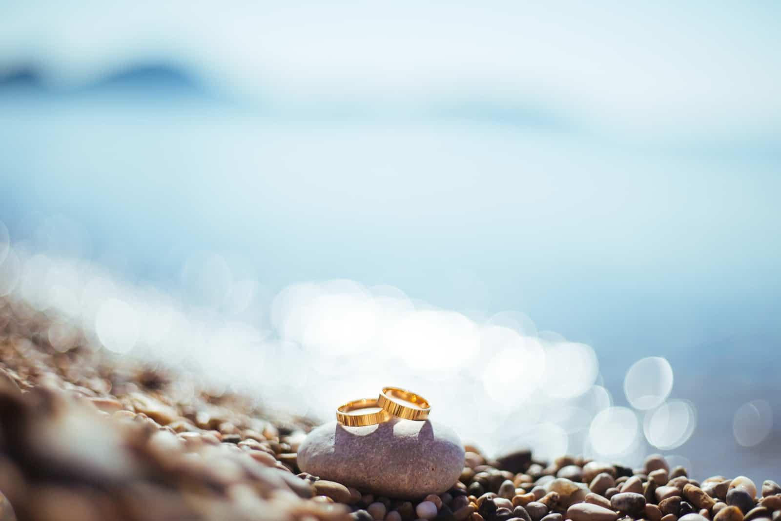 Goldene Eheringe auf den Seekieseln