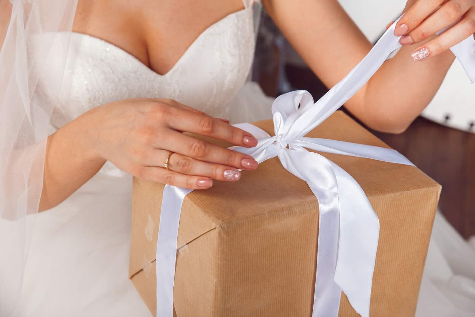 Hände mit Geschenkbox auf der Hochzeitsfeier