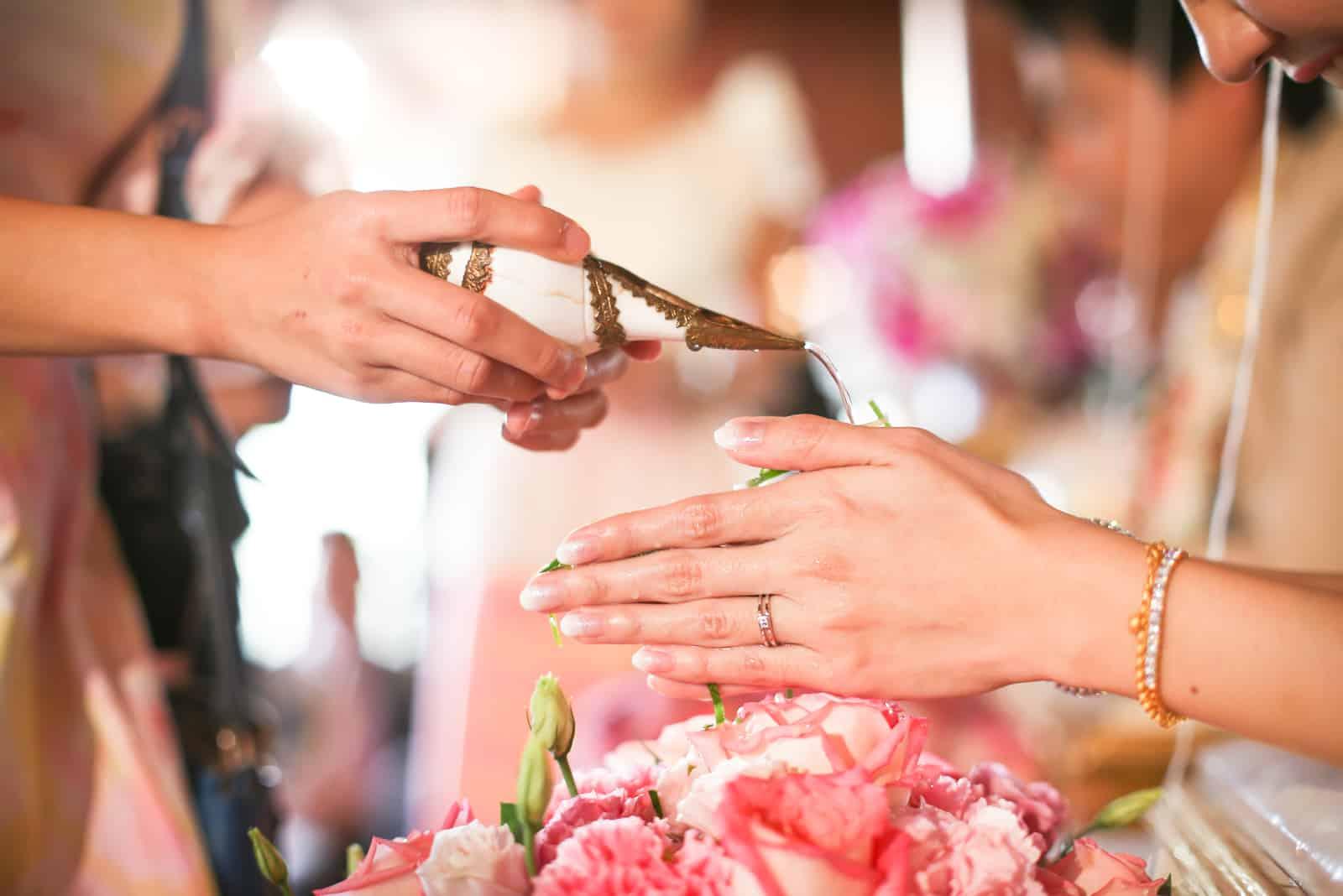Hände, die Segenwasser in Brautbänder gießen, thailändische Hochzeit