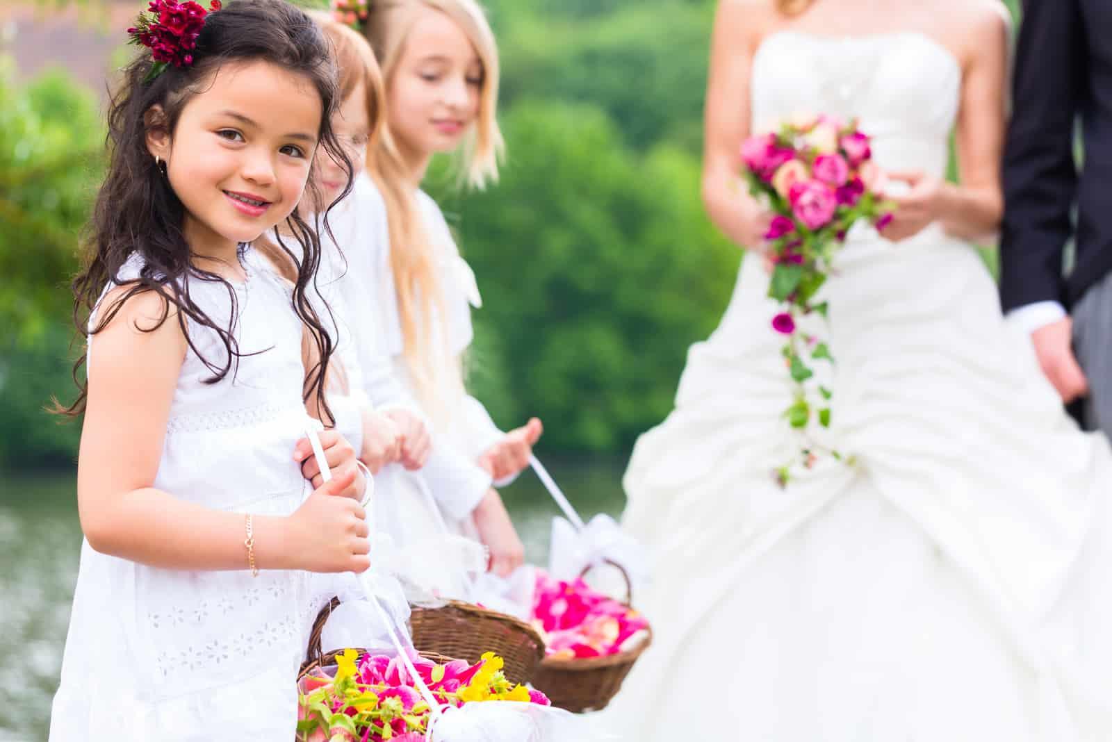 Hochzeit Braut und Bräutigam mit Blumenkindern oder Brautjungfer im weißen Kleid