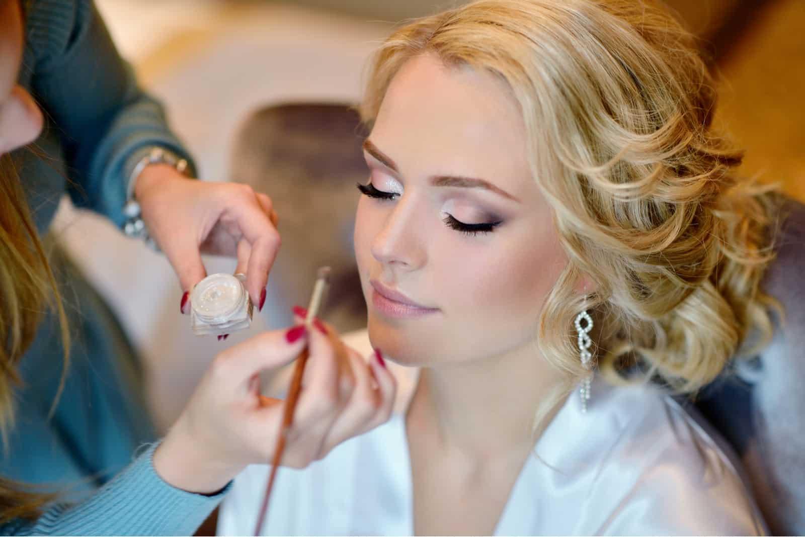 Hochzeits-Maskenbildner machen ein Make-up für die Braut