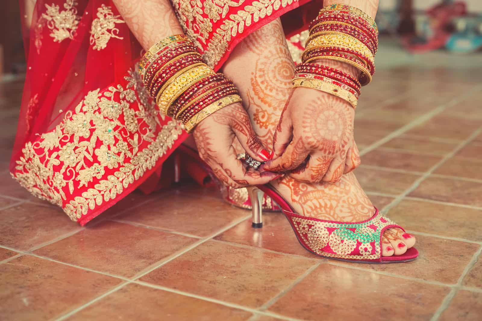 Hochzeitsentwurf auf den Füßen und Händen der roten gekleideten Braut