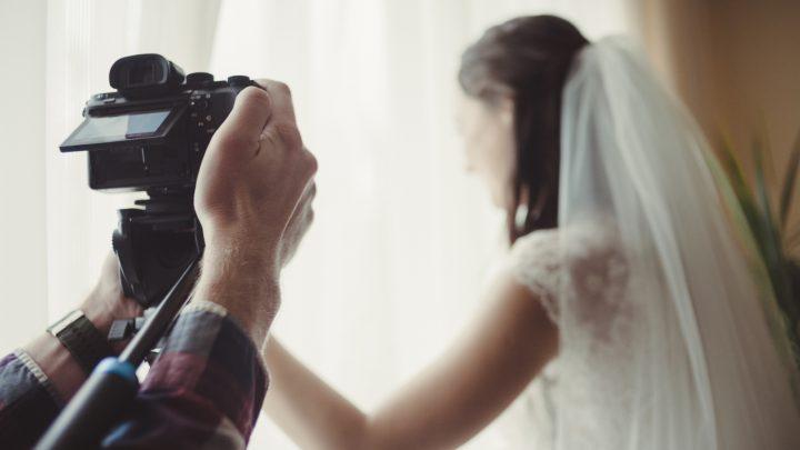Der Kameramann nimmt die Braut auf, die aus dem Fenster schaut