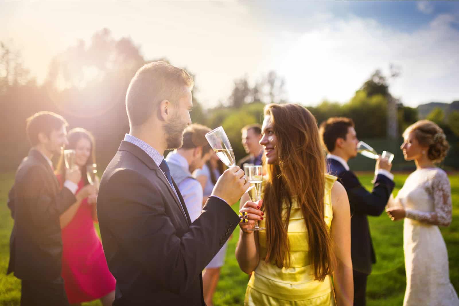 Hochzeitsgäste genießen Champagner bei Sonnenuntergang