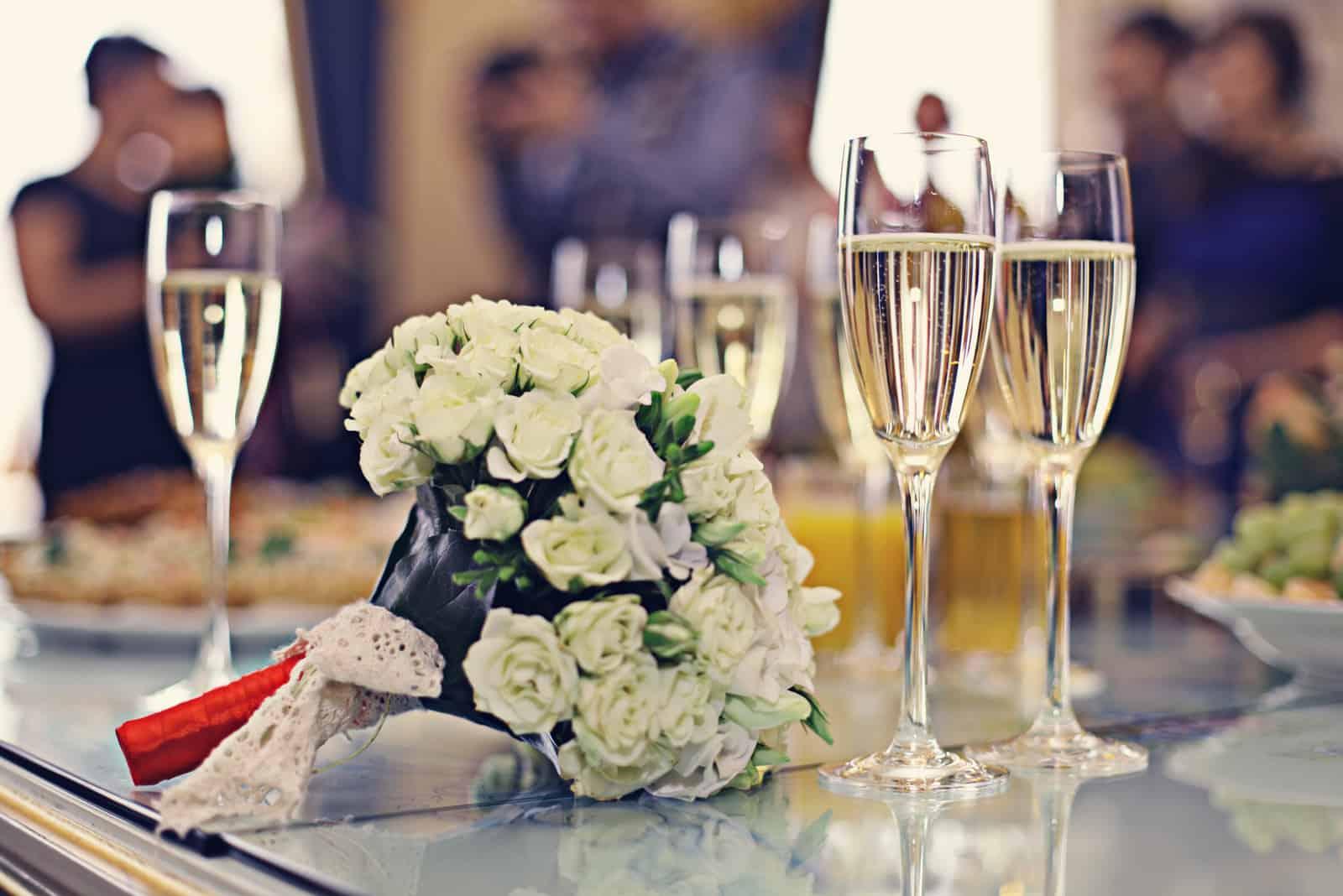 Hochzeitsstrauß und Champagner auf dem Tisch