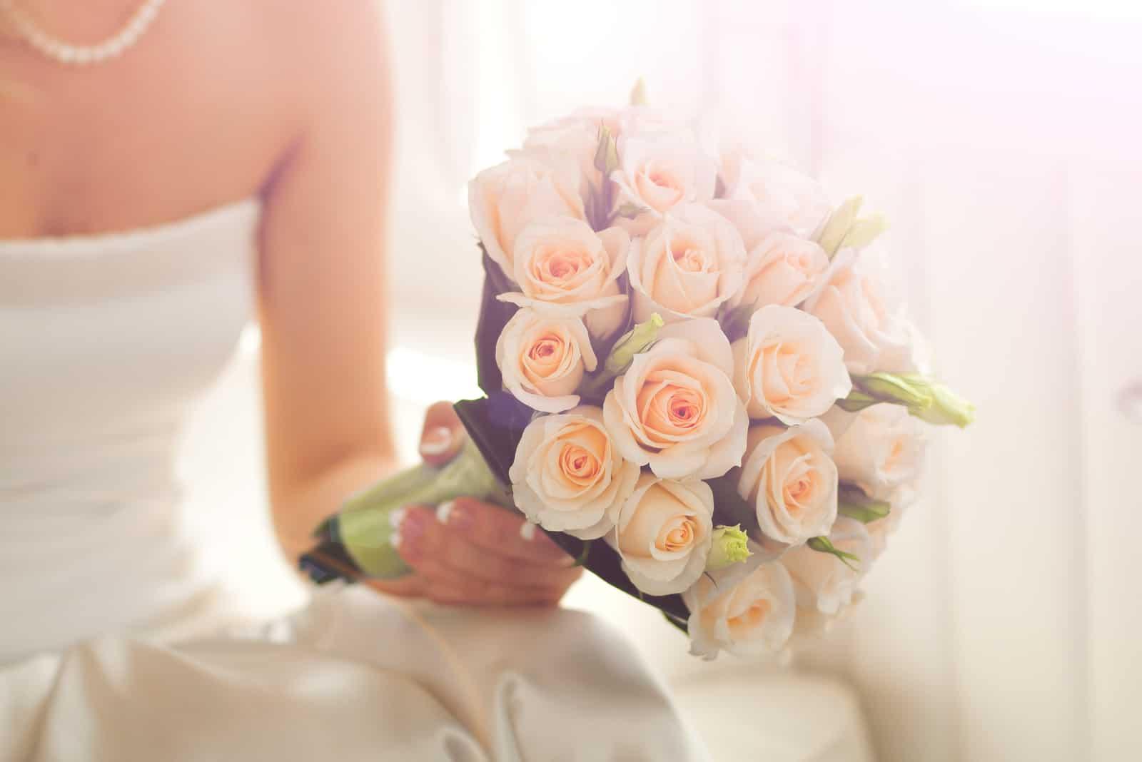 Hochzeitsstrauß von Rosen in der Hand der Braut
