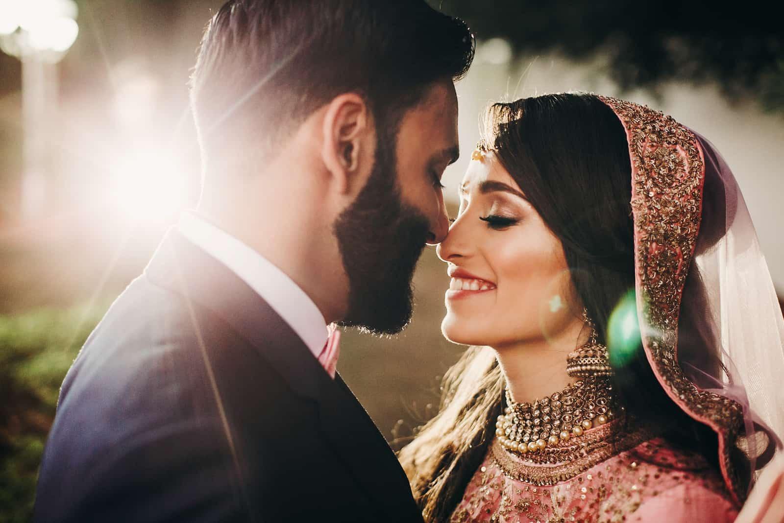 Hübscher bärtiger indischer Bräutigam küsst Braut im rosa Kleid zart stehend outisde