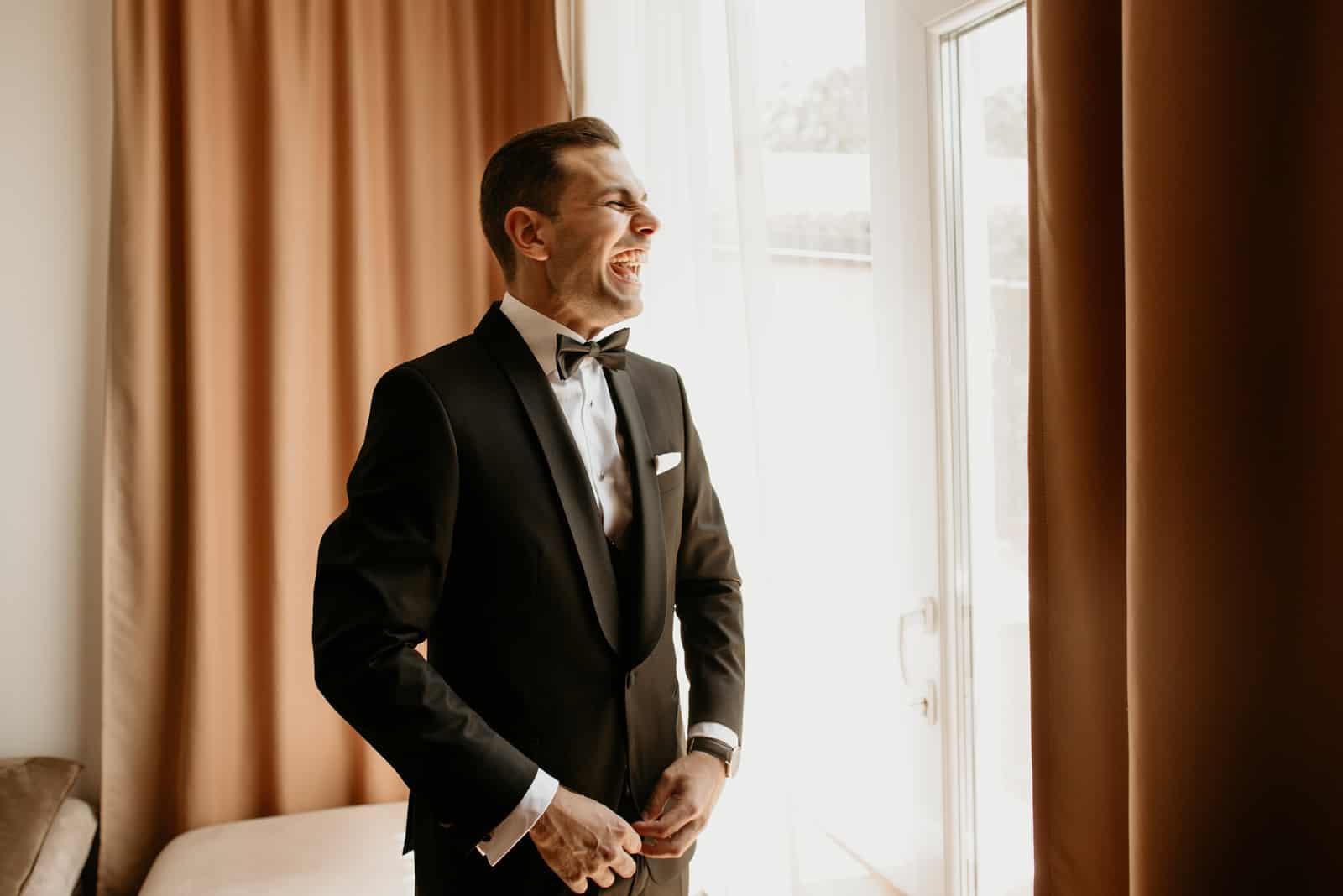 Hübscher Mann, der im Anzug aufwirft