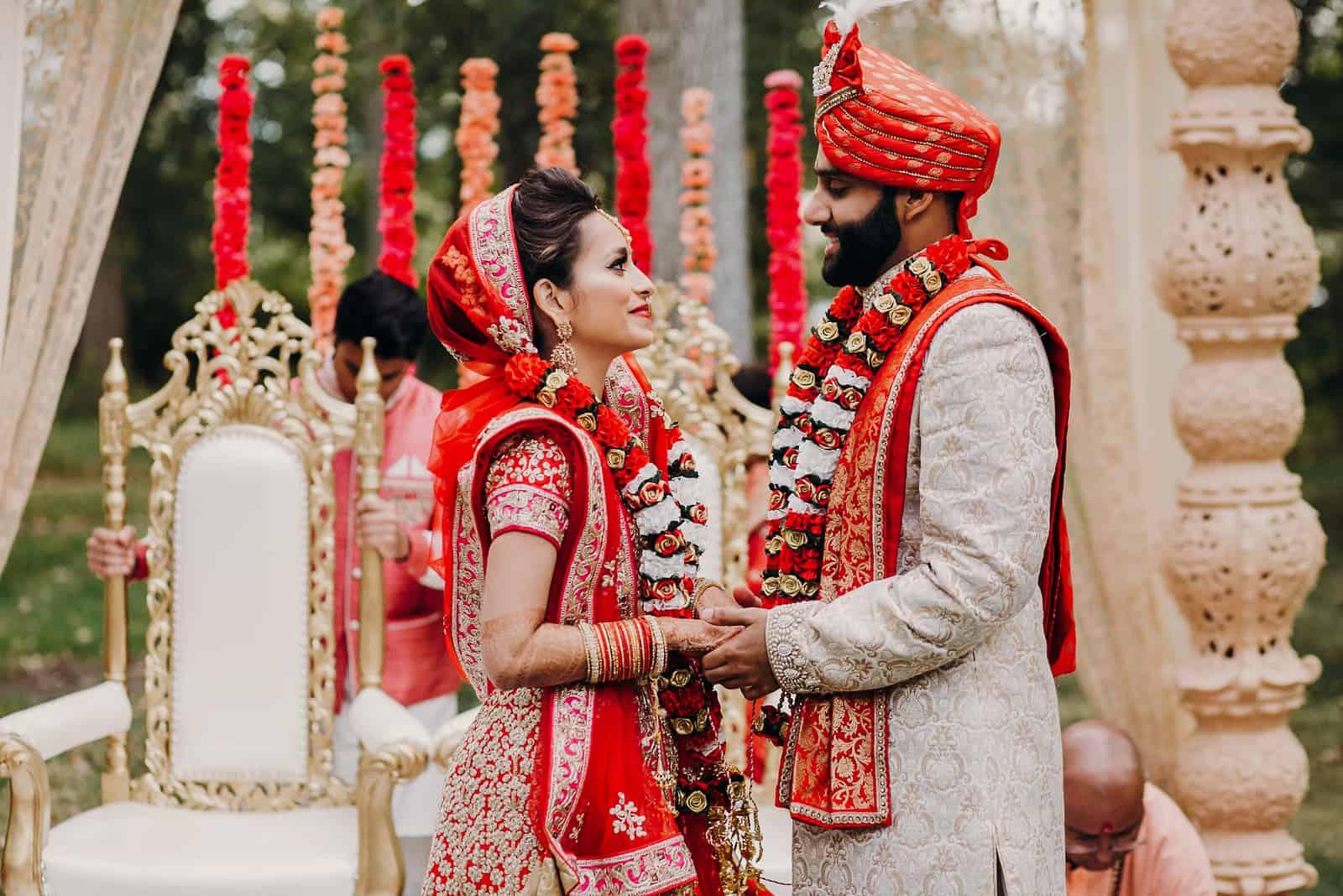 Indischer Bräutigam gekleidet in weißem Sherwani und rotem Hut mit atemberaubender Braut in roter Lehenga