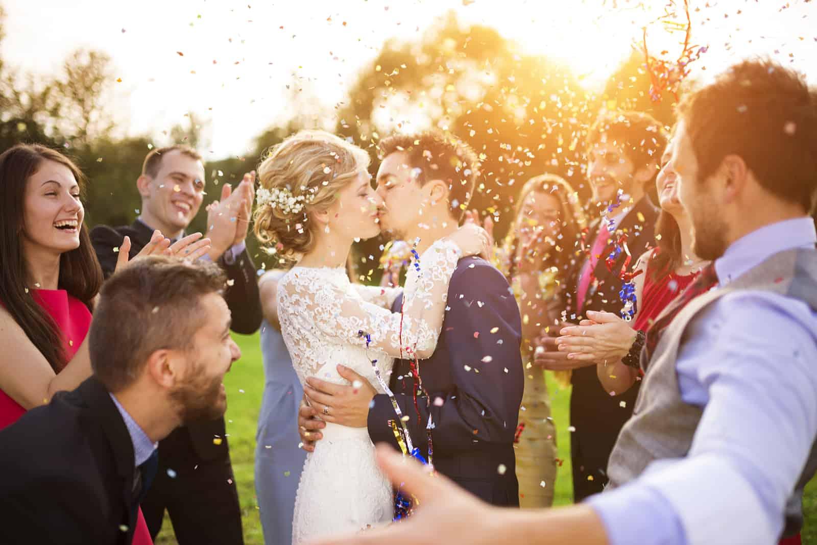 Jungvermähltenpaar und ihre Freunde auf der Hochzeitsfeier duschten mit Konfetti im grünen, sonnigen Park