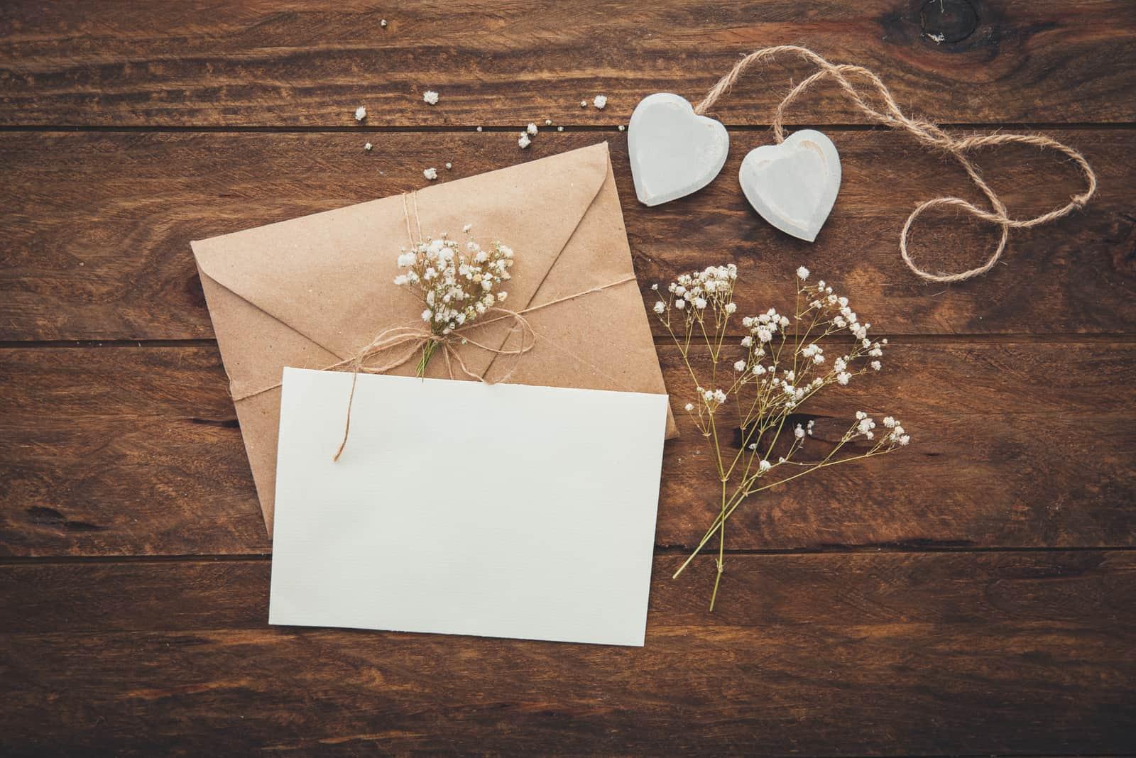 Leere Grußkarte und Blumen mit Herzen auf hölzernem Hintergrund