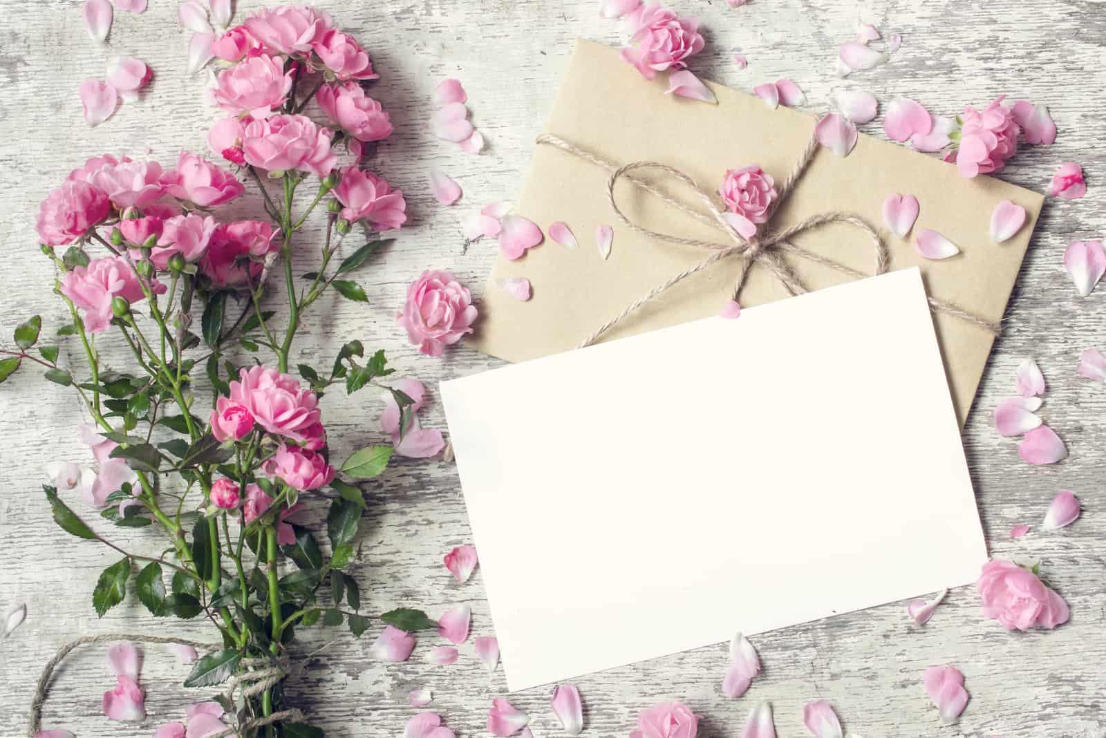 Leere weiße Grußkarte und Umschlag mit rosa Rosenblüten