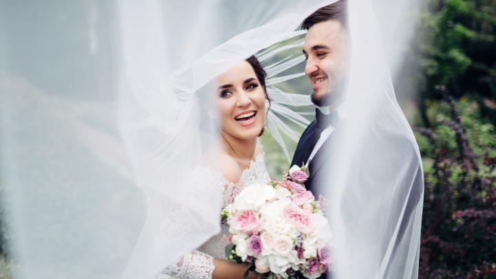 ein lächelndes Hochzeitspaar umarmt und lacht