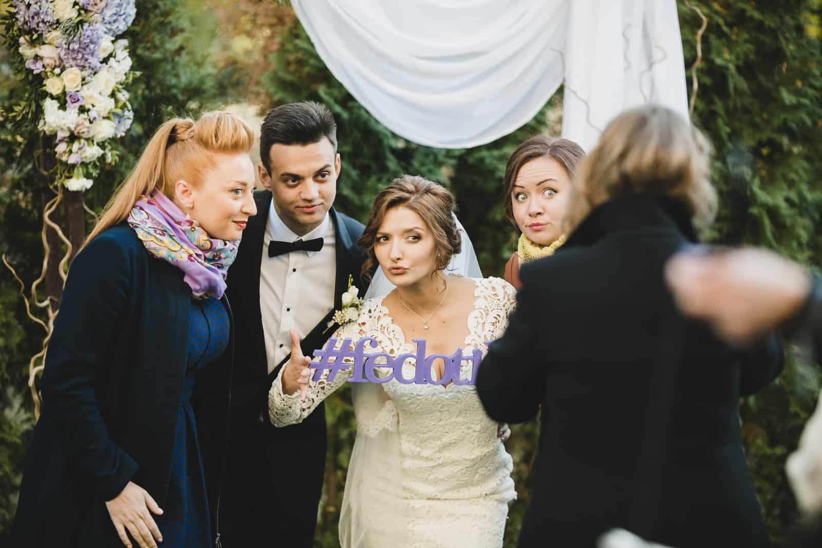 Lustige Jungvermählten und Freunde machen ein Bild mit Freunden, die einen hölzernen Hochzeitshashtag in ihren Armen halten