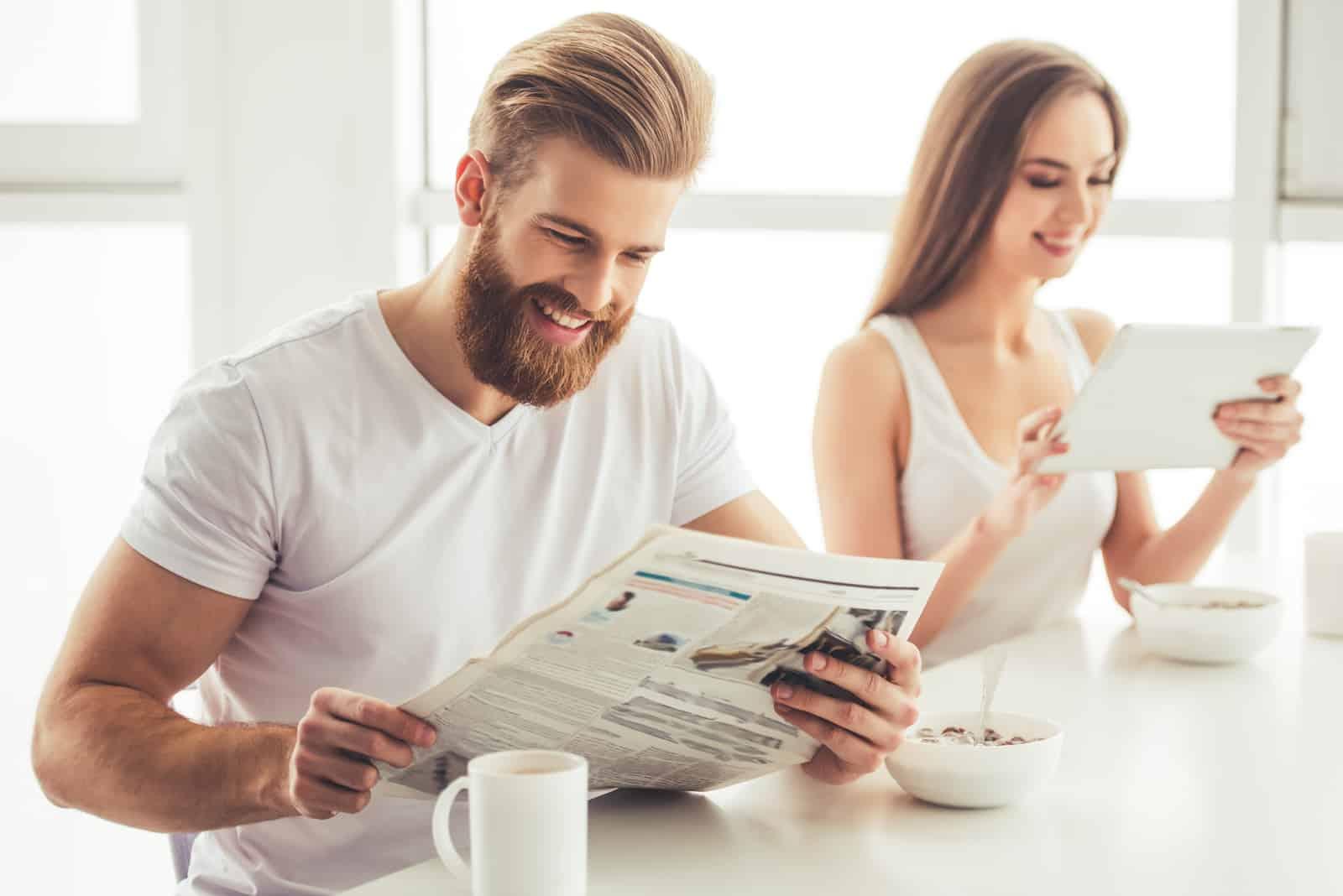 Mädchen benutzt ein digitales Tablet, Mann liest eine Zeitung