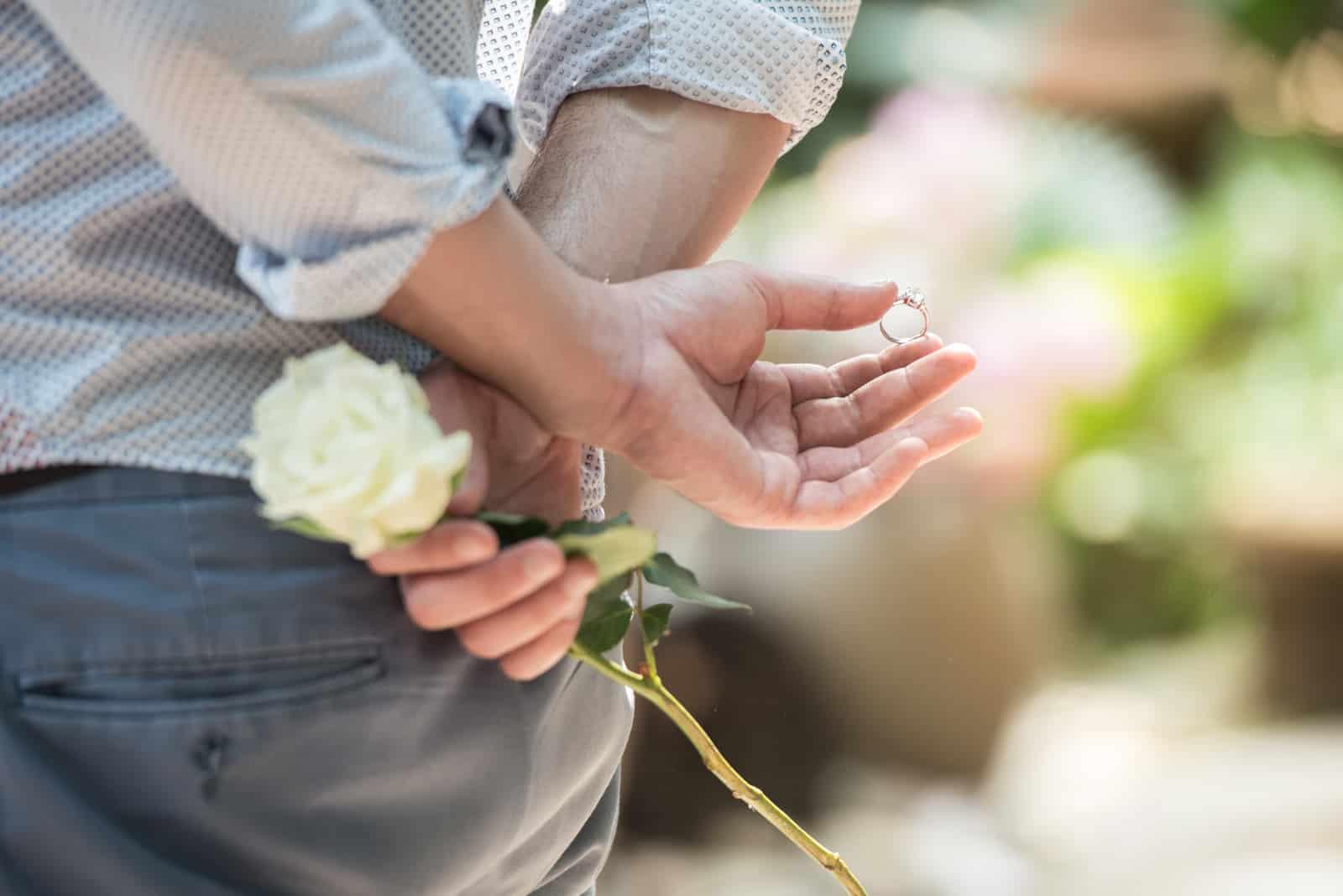 Männer verstecken den Ring und weiße Rose hinter sich überrascht