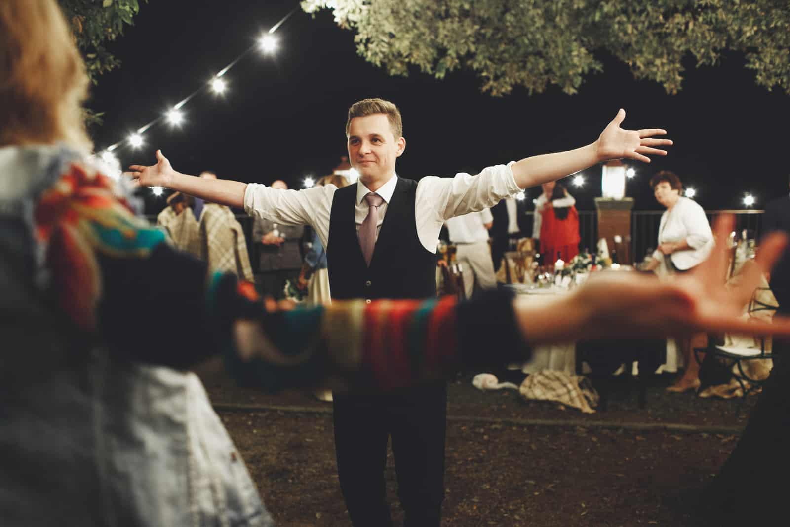 Mann im schwarzen Anzug hält seine Arme weit vor einem Tanz