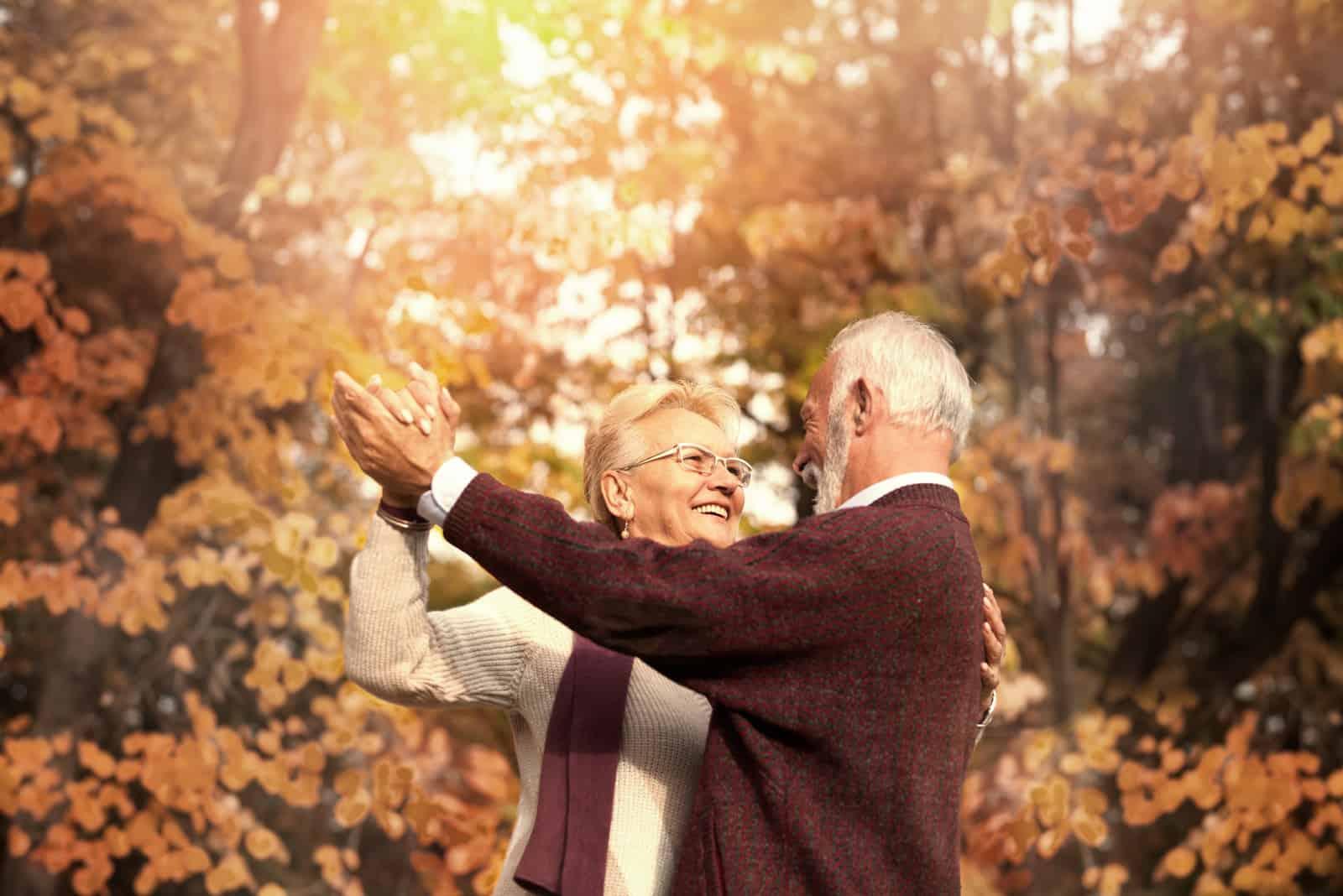 Nettes älteres Paar, das im Herbsttag tanzt