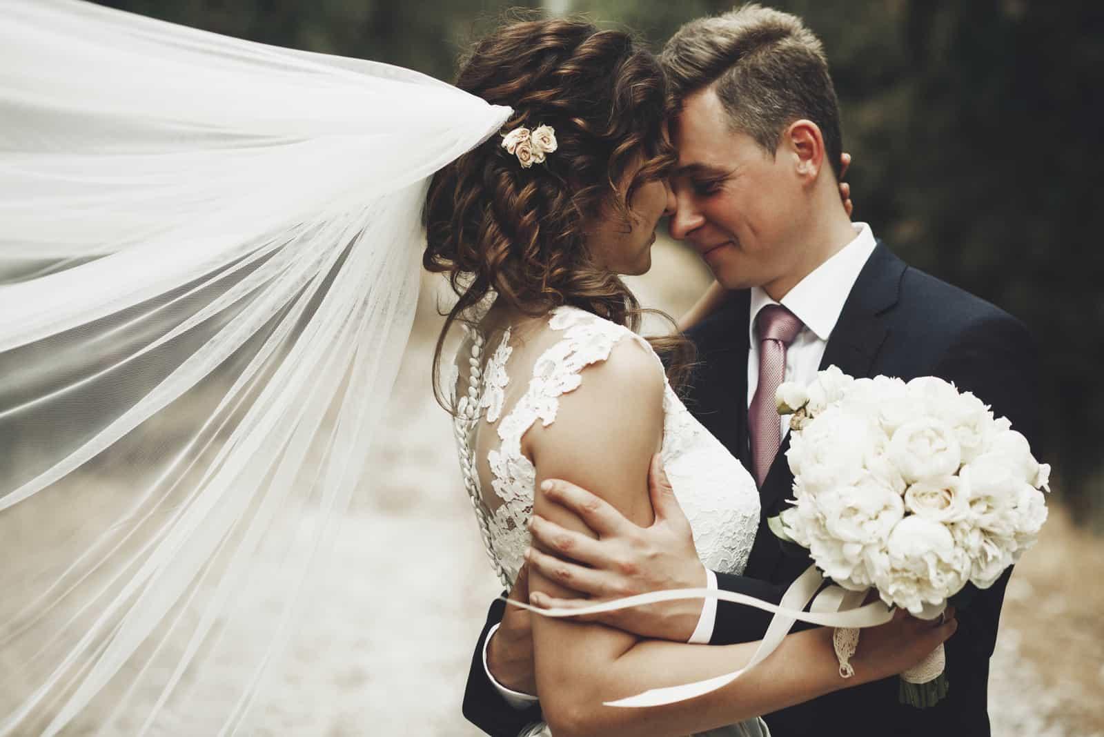 Porträt der glücklichen neuen Frau und des Ehemanns, die draußen umarmen und lächeln