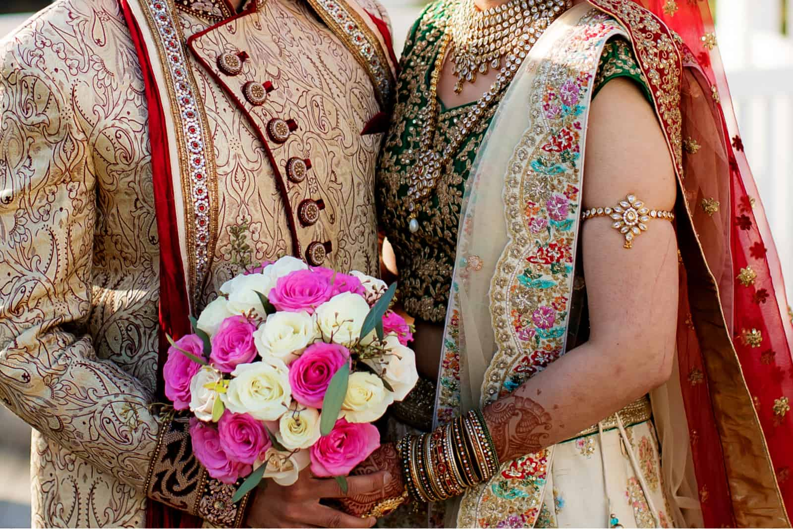 Romantisches indisches Paar, das Hochzeitsbouqet hält und Hochzeitstag aufwirft