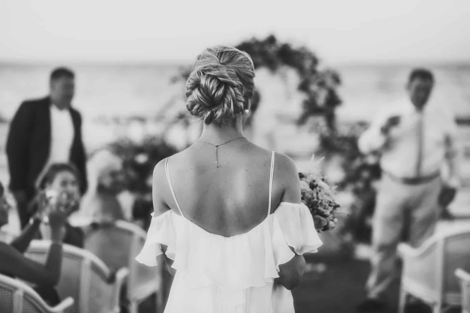 Schauen Sie von hinten auf wunderschöne Braut im Sommerkleid