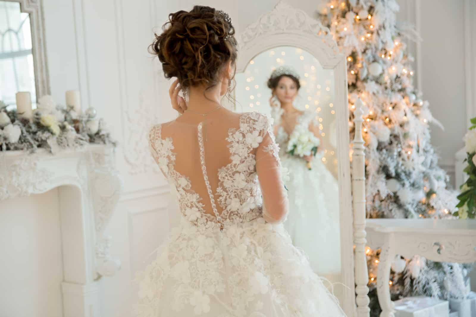 Schöne Braut in einem Hochzeitskleid an einem Spiegel