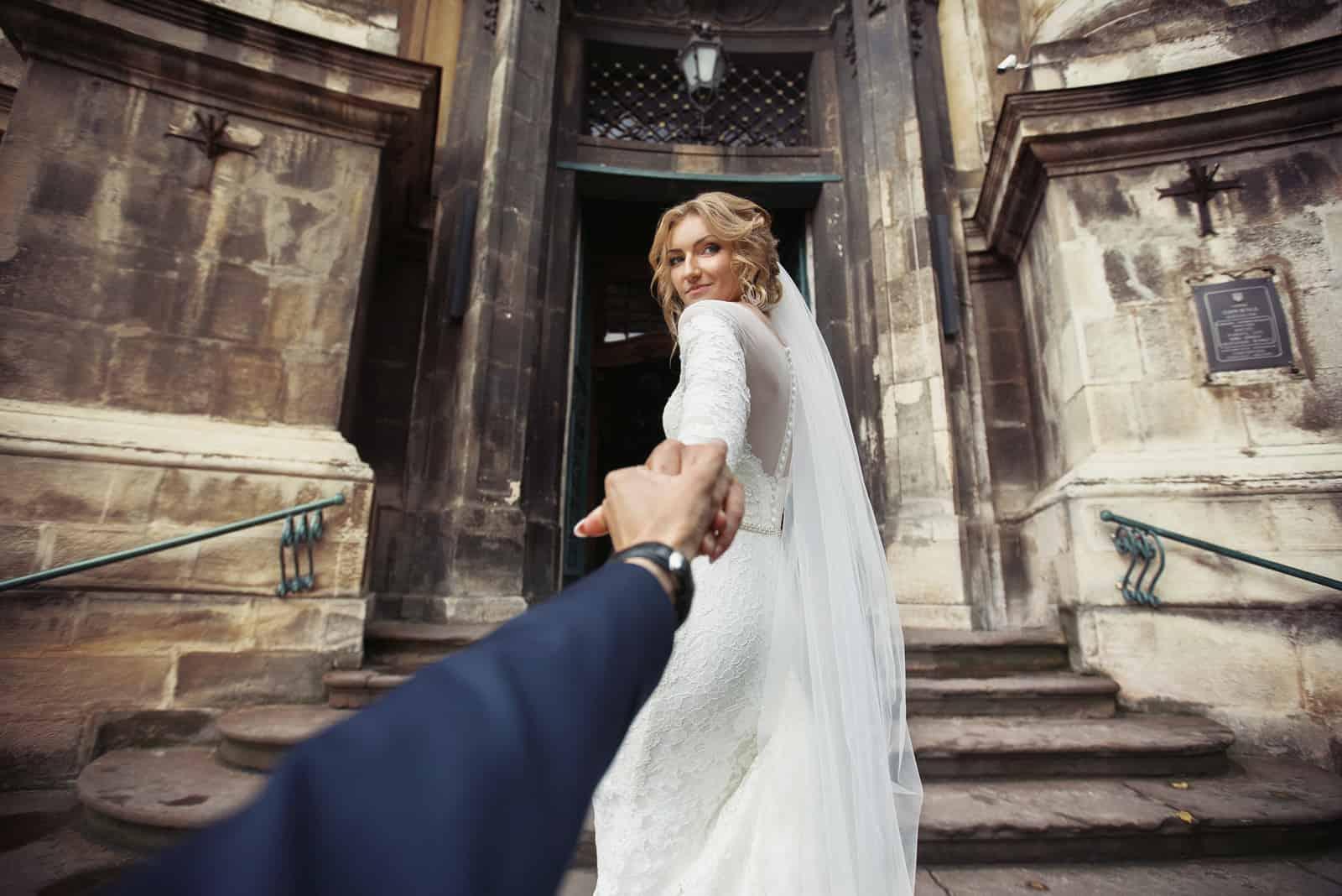 Schöne stilvolle Braut, die Bräutigam zur Kirche für Hochzeit führt