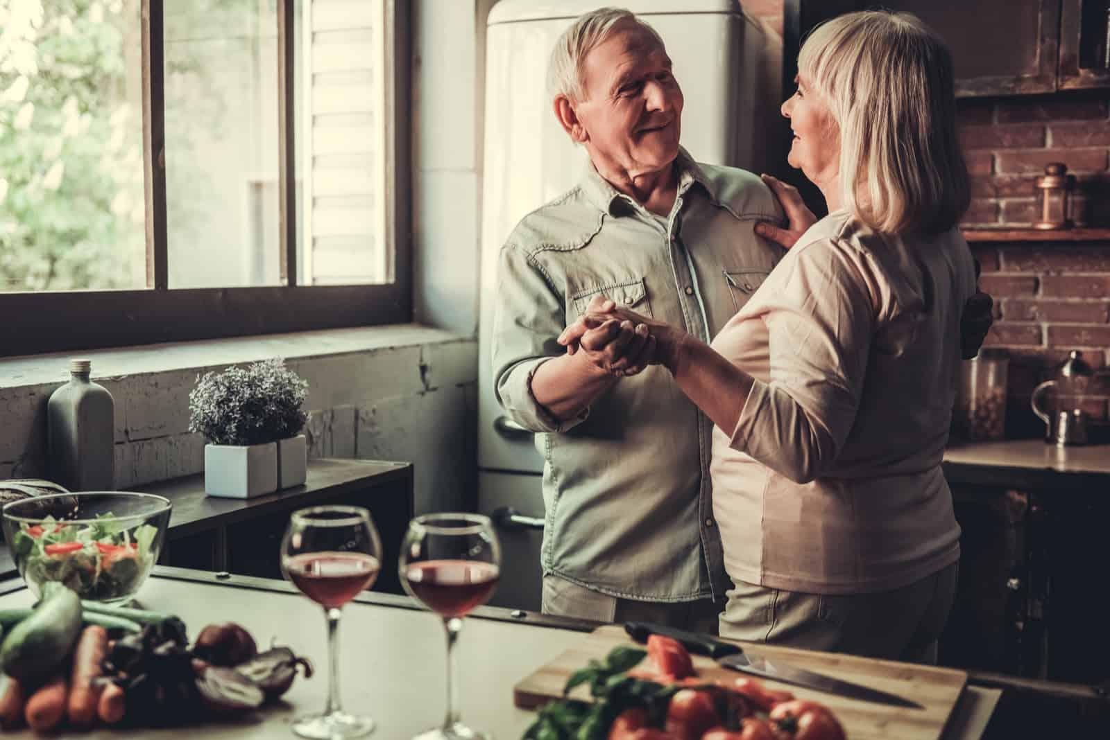 Schönes älteres Paar tanzt und lächelt beim gemeinsamen Kochen in der Küche