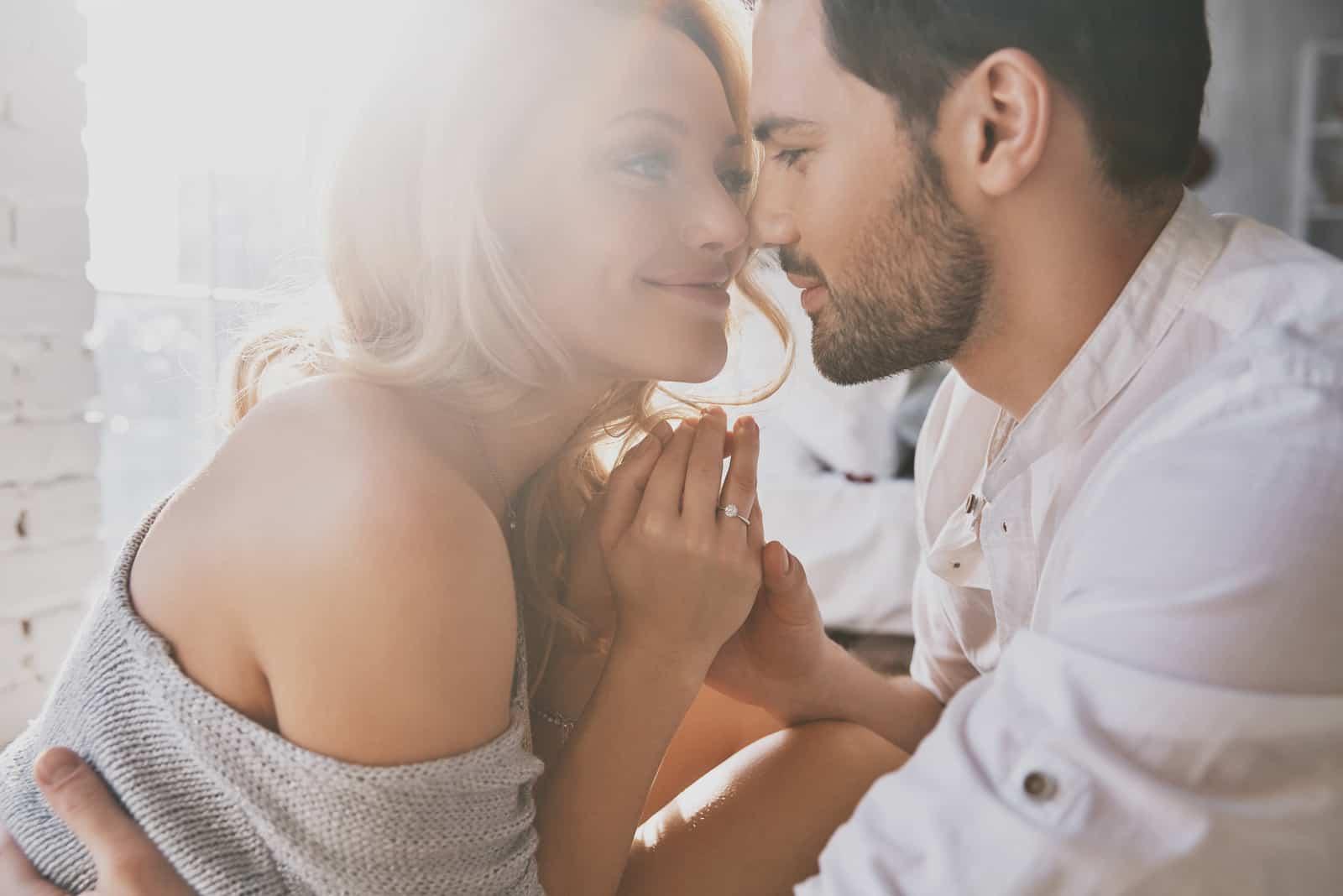 Schönes junges Paar, das sich beim Sitzen im Schlafzimmer verbindet und lächelt
