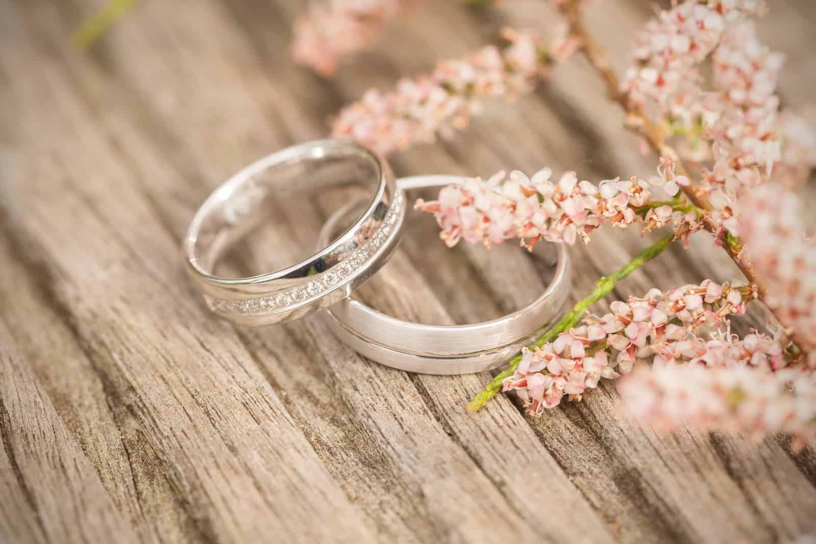 Silberne Eheringe auf einem hölzernen Hintergrund