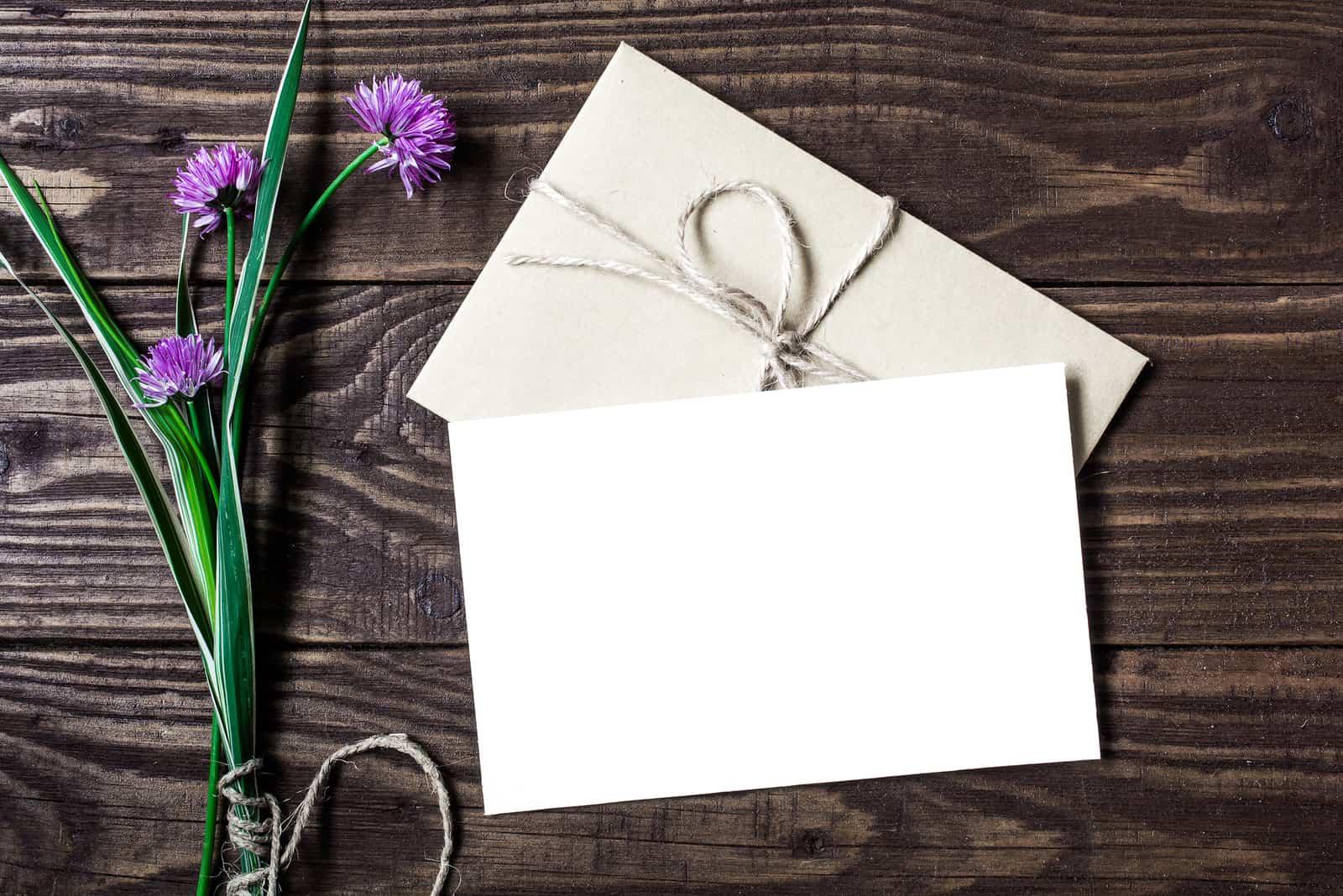 Strauß lila Wildblumen und leere weiße Grußkarte