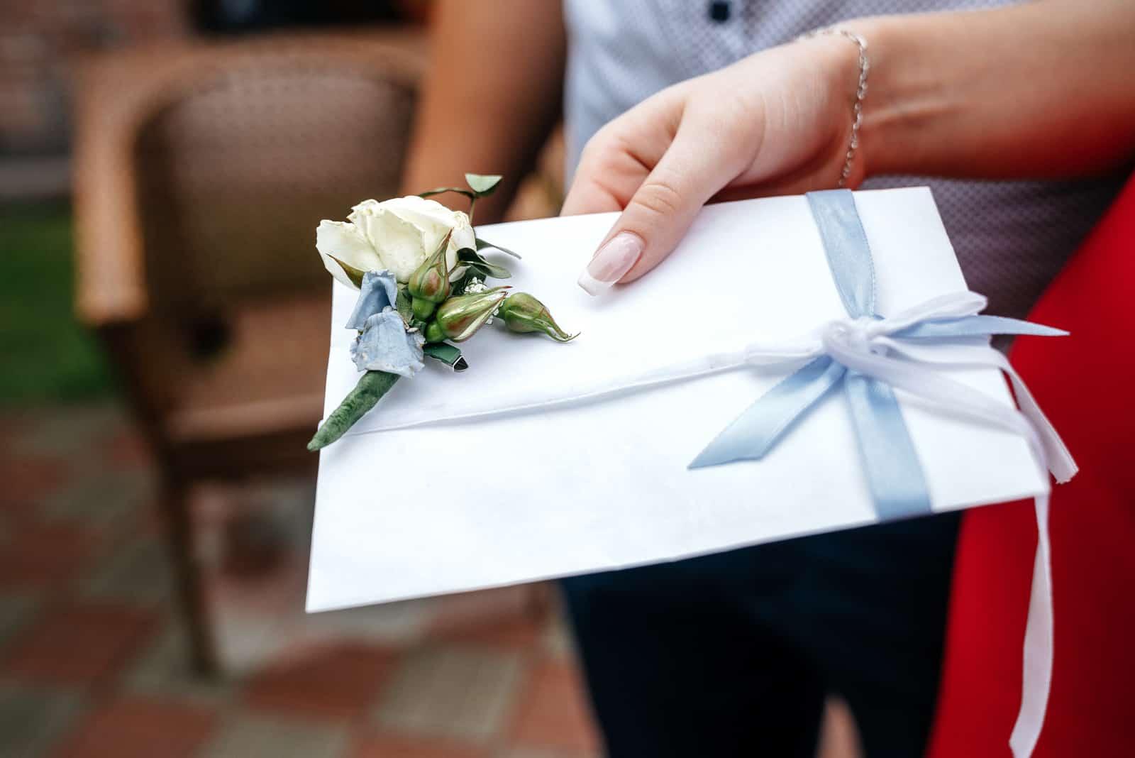 Weißer Hochzeitsumschlag mit einem Boutonniere in der Hand einer Frau
