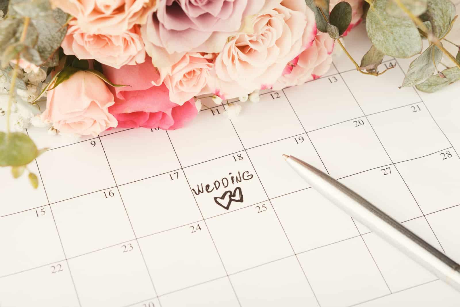 Worthochzeit und zwei Herzen auf Kalender mit süßem Rosenstrauß.